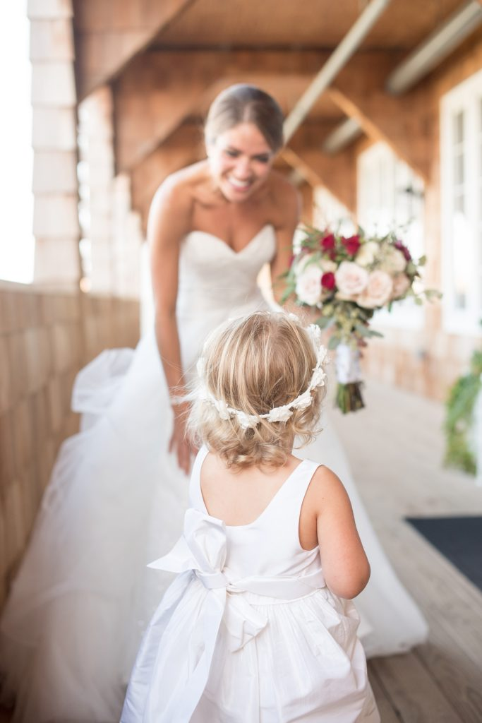 Mikkel Paige Photography photos of a Bay Head Yacht Club nautical wedding. The bride greets the flower girl in her white floral crown.