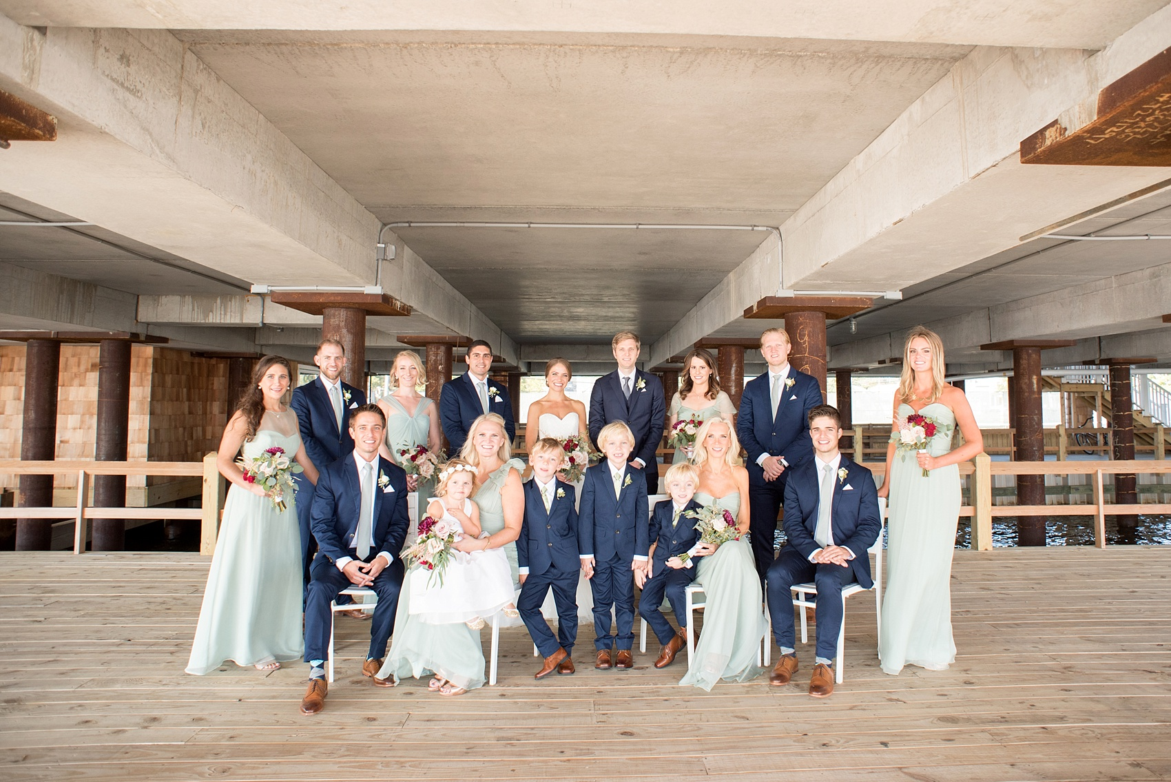 Mikkel Paige Photography photos of a Bay Head Yacht Club nautical wedding. The bride wore a white sweetheart gown and her bridesmaids wore mint green Amsale gowns. The groomsmen wore navy blue suits and grey ties.