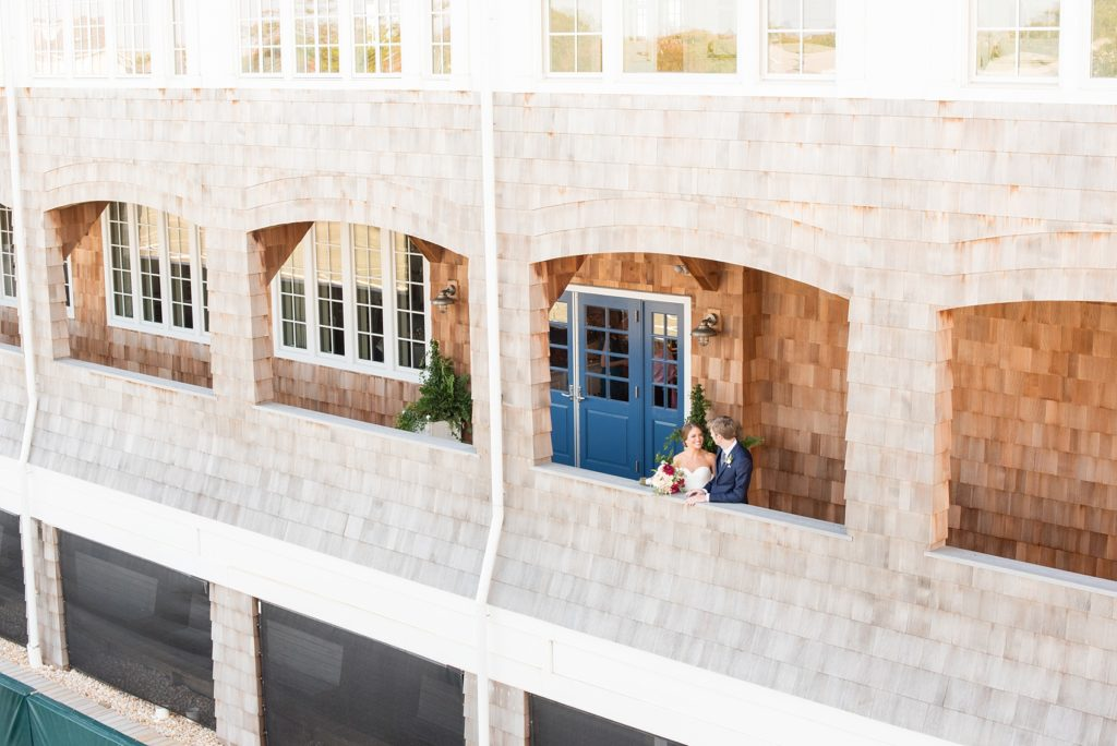 Mikkel Paige Photography photos of a Bay Head Yacht Club nautical wedding. The bride and groom are captured in a wide-view image of the wooden shingle sided waterview venue.