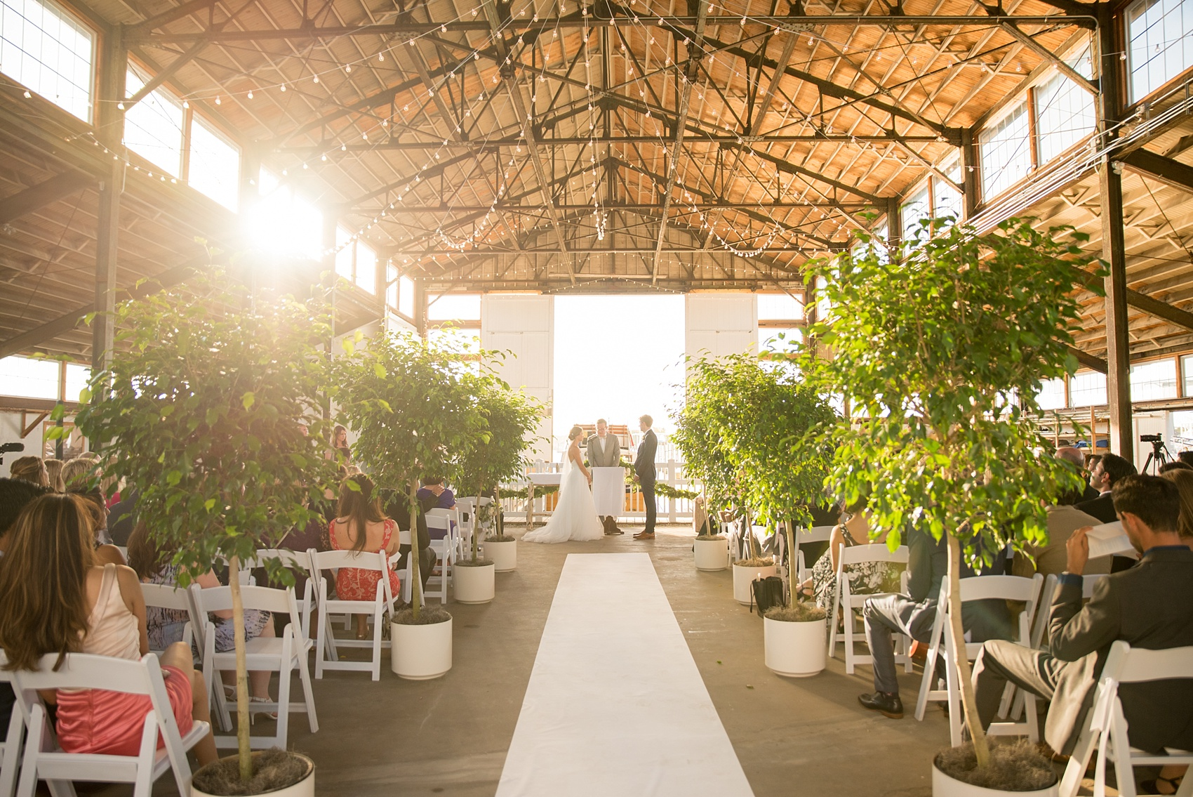 Mikkel Paige Photography picture of a Bay Head Yacht Club nautical wedding. A boathouse ceremony with ficus trees lining the aisle and vintage boat exit.