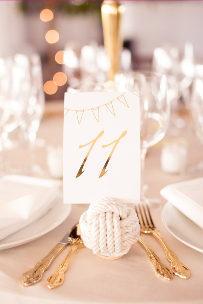 Mikkel Paige Photography picture of a Bay Head Yacht Club nautical wedding. Gold table numbers were help in white rope spheres next to gold flatware.