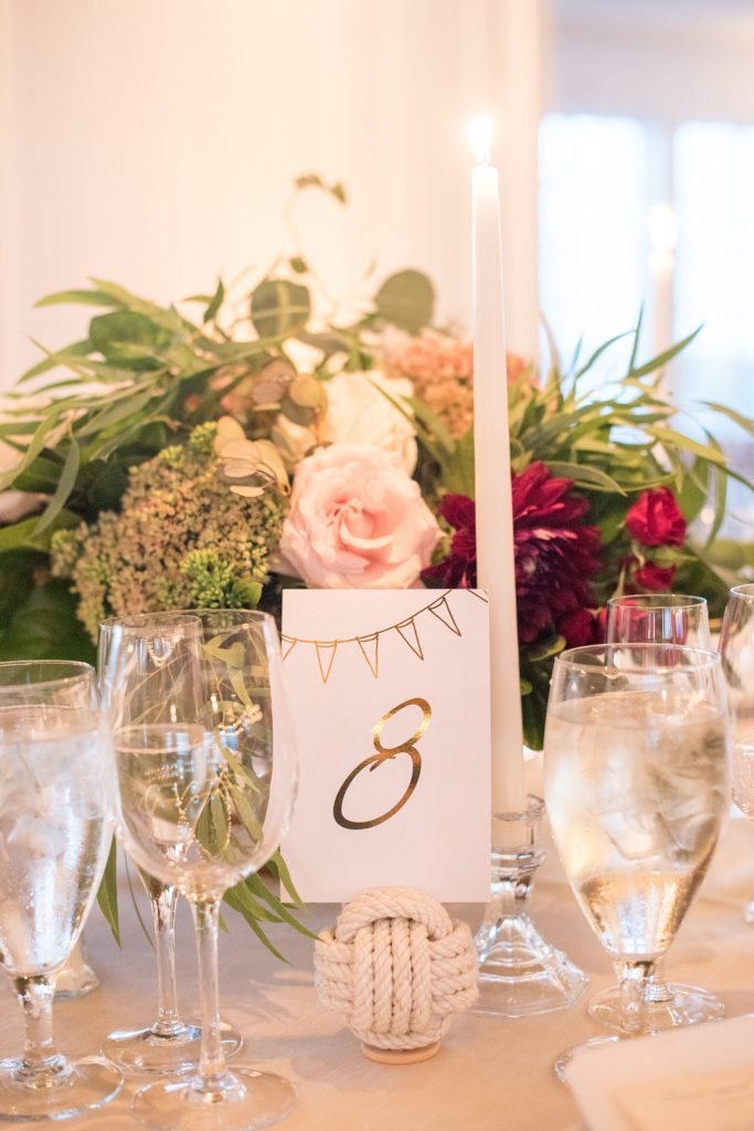 Mikkel Paige Photography picture of a Bay Head Yacht Club nautical wedding. Gold table numbers were help in white rope spheres next to gold flatware with fall colored floral centerpieces and tapered candles.