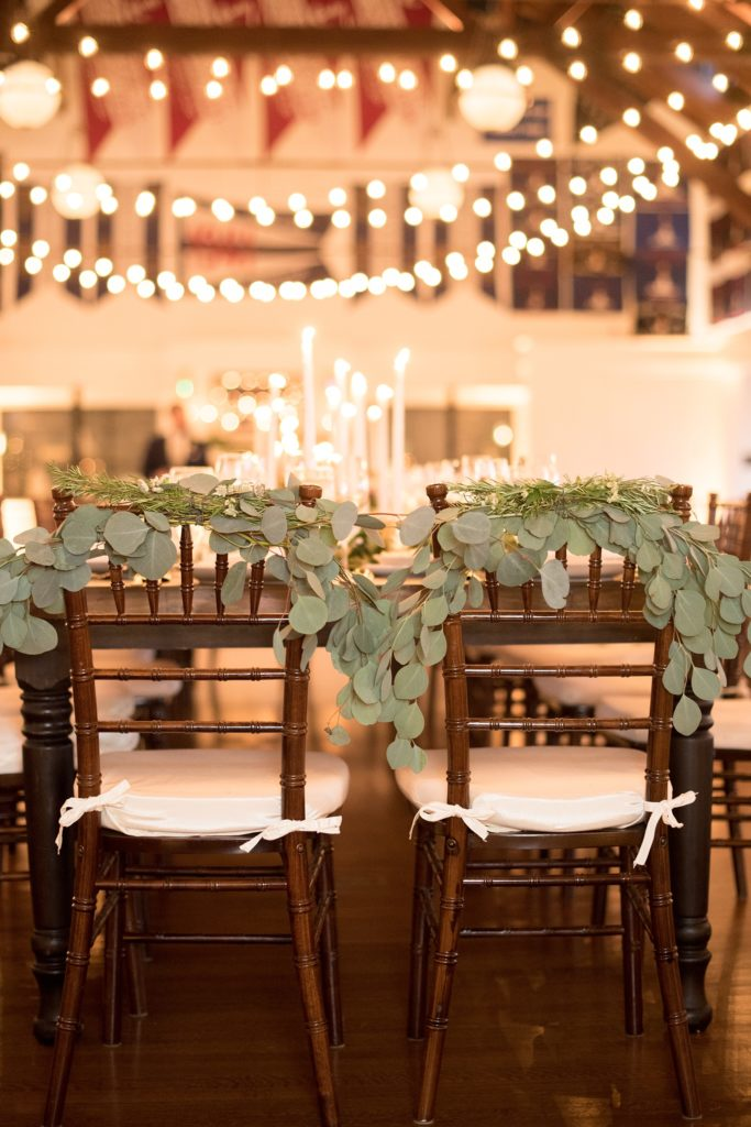 Mikkel Paige Photography picture of a Bay Head Yacht Club nautical wedding. Their bride and groom chairs were decorated with eucalyptus greenery and room lit with bistro lights.