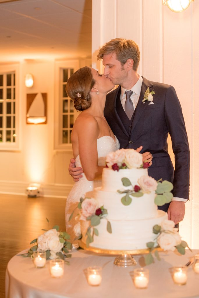 Mikkel Paige Photography photo of the cake cutting at a wedding at Bay Head Yacht Club on the water in New Jersey. White buttercream tiered cake with fall flowers.
