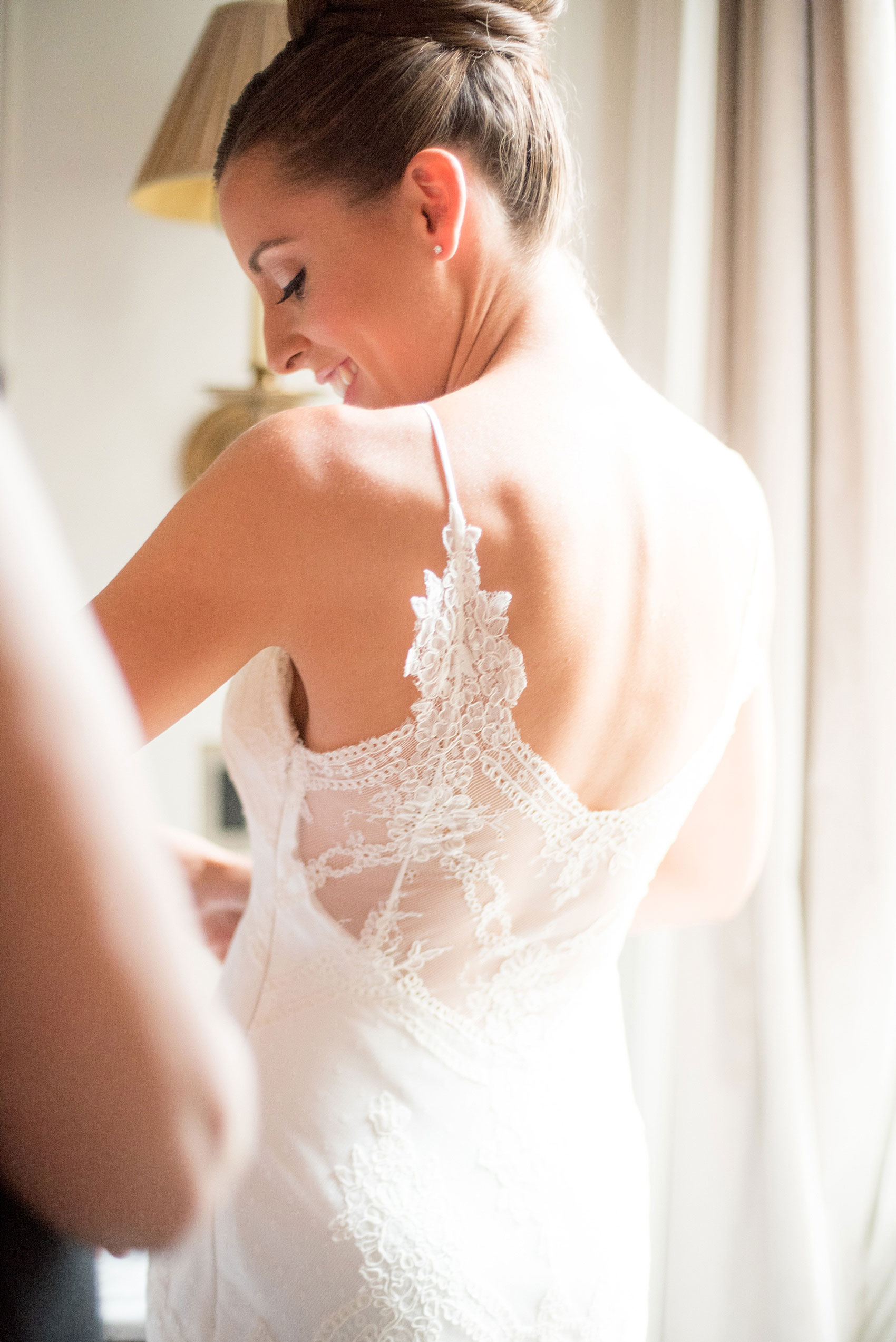 Mikkel Paige Photography captures a luxury wedding in NYC. The bride's mom helps her get dressed in her David Fielden wedding from Kleinfeld's at The Marlton Hotel.