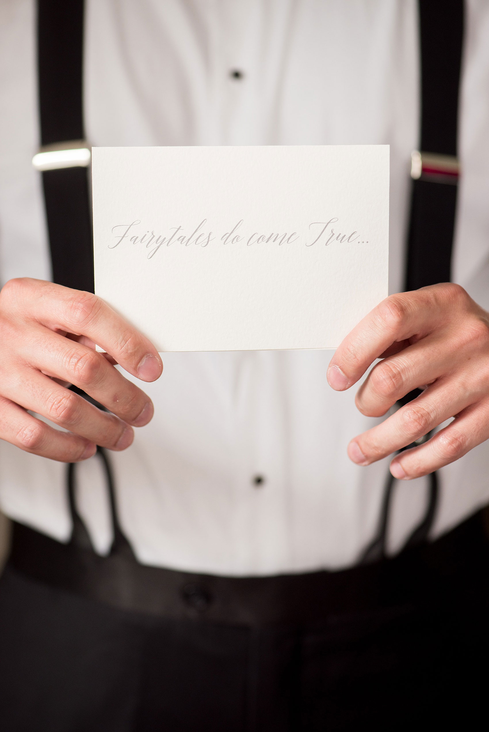 "Mikkel Paige Photography photos of a luxury wedding in NYC. Image of the groom holding his ""Fairy tales do come true..."" calligraphy card."