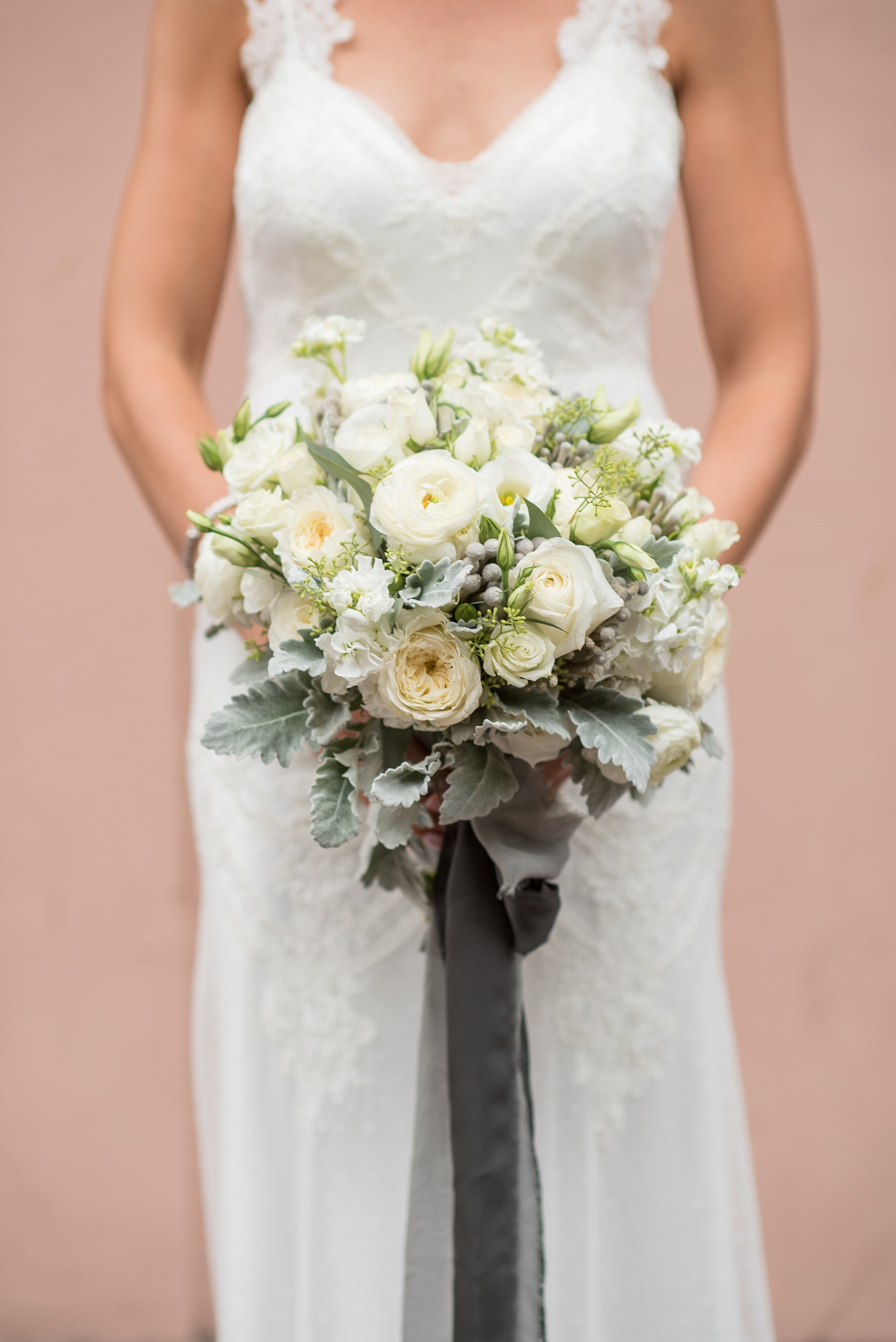Mikkel Paige Photography photos of a luxury wedding in NYC. Portrait picture of the bride in her form fitting David Fielden wedding gown from Kleinfeld's, holding her white bouquet with ranunculus and brunia.