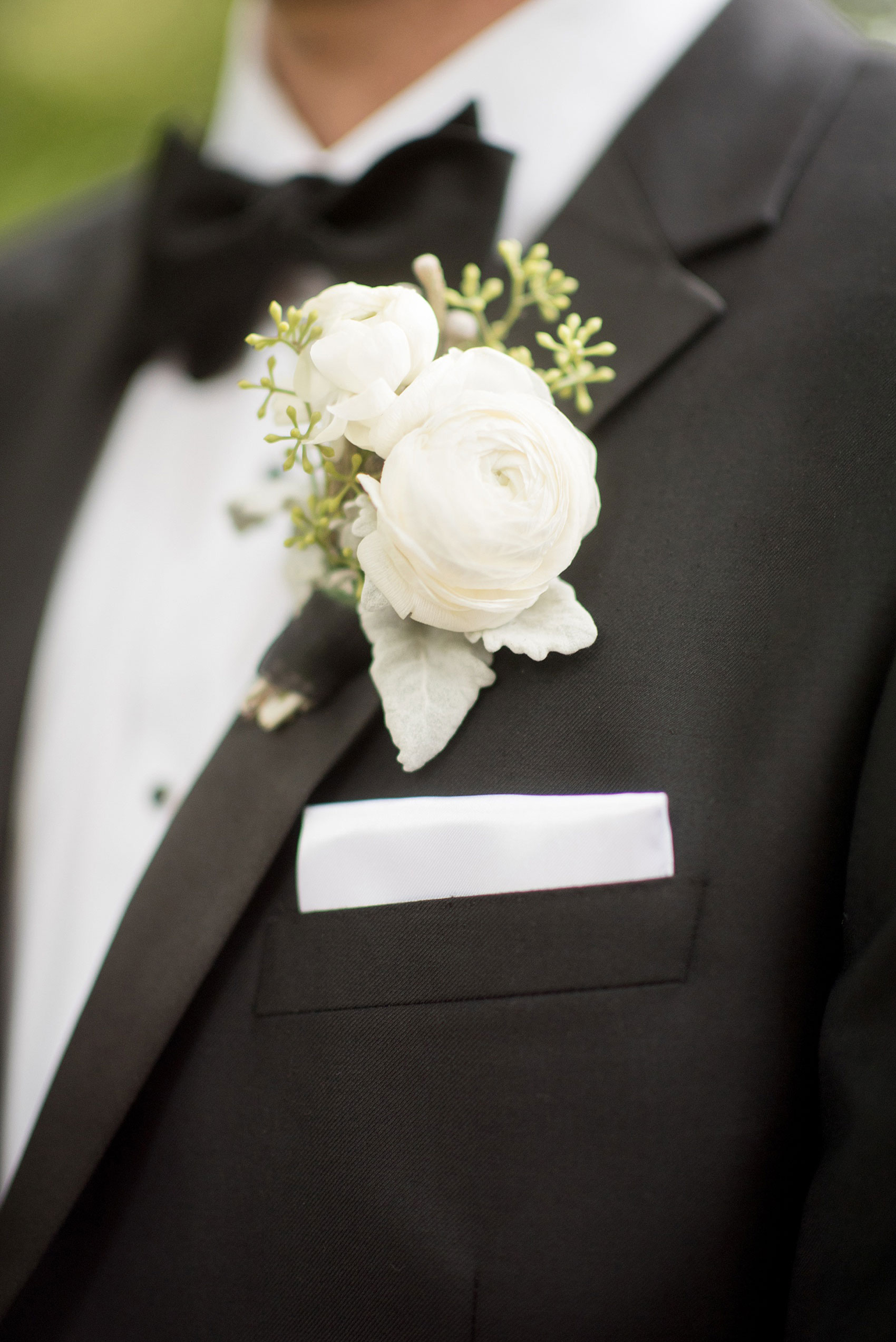 Mikkel Paige Photography photos of a luxury wedding in NYC. Image of the groom's white ranunculus boutonniere.