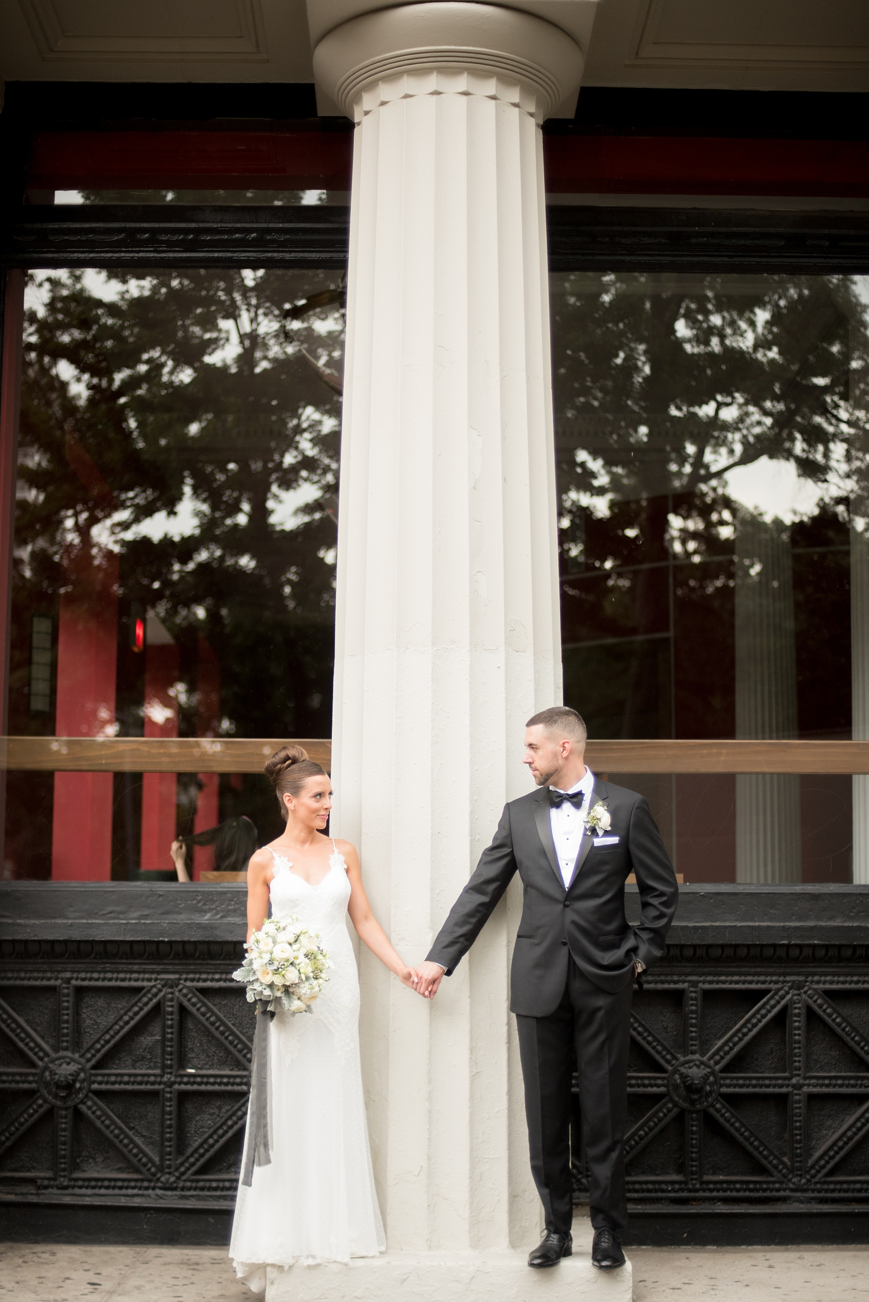 Mikkel Paige Photography photos of a luxury wedding in NYC. Image of the bride and groom near Washington Square Park with white columns.