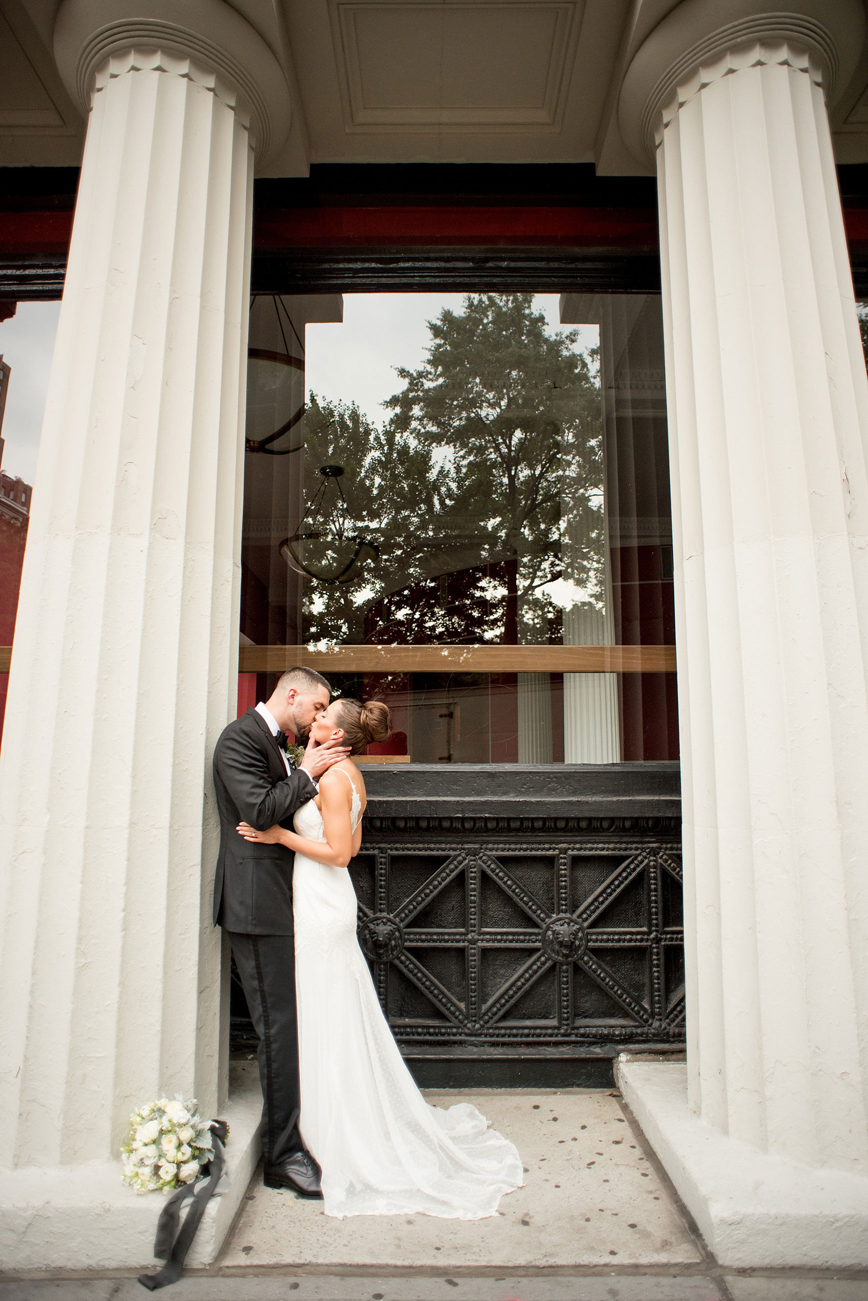 Mikkel Paige Photography photos of a luxury wedding in NYC. Image of the bride and groom near Washington Square Park kissing between white columns.