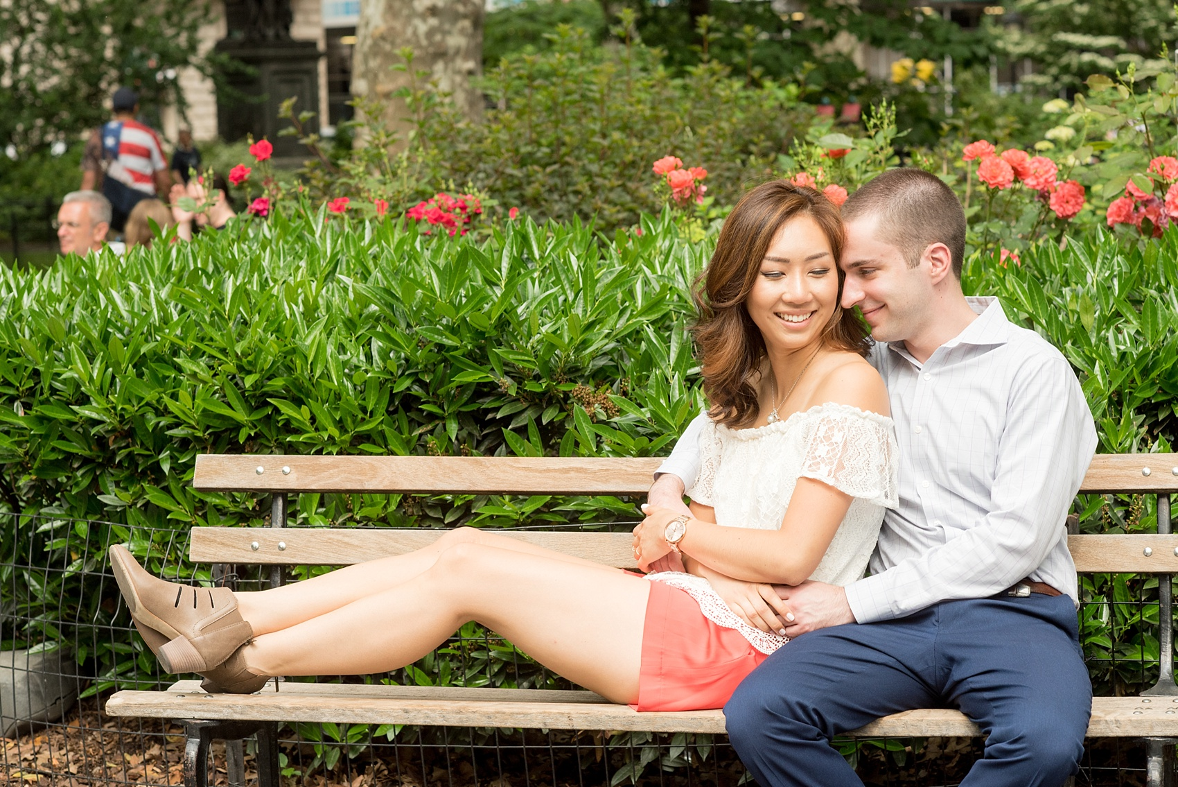 Mikkel Paige Photography photos of a Madison Square Park engagement session in NYC during spring. The bride wore an off-the-shoulder white lace top and orange shorts.