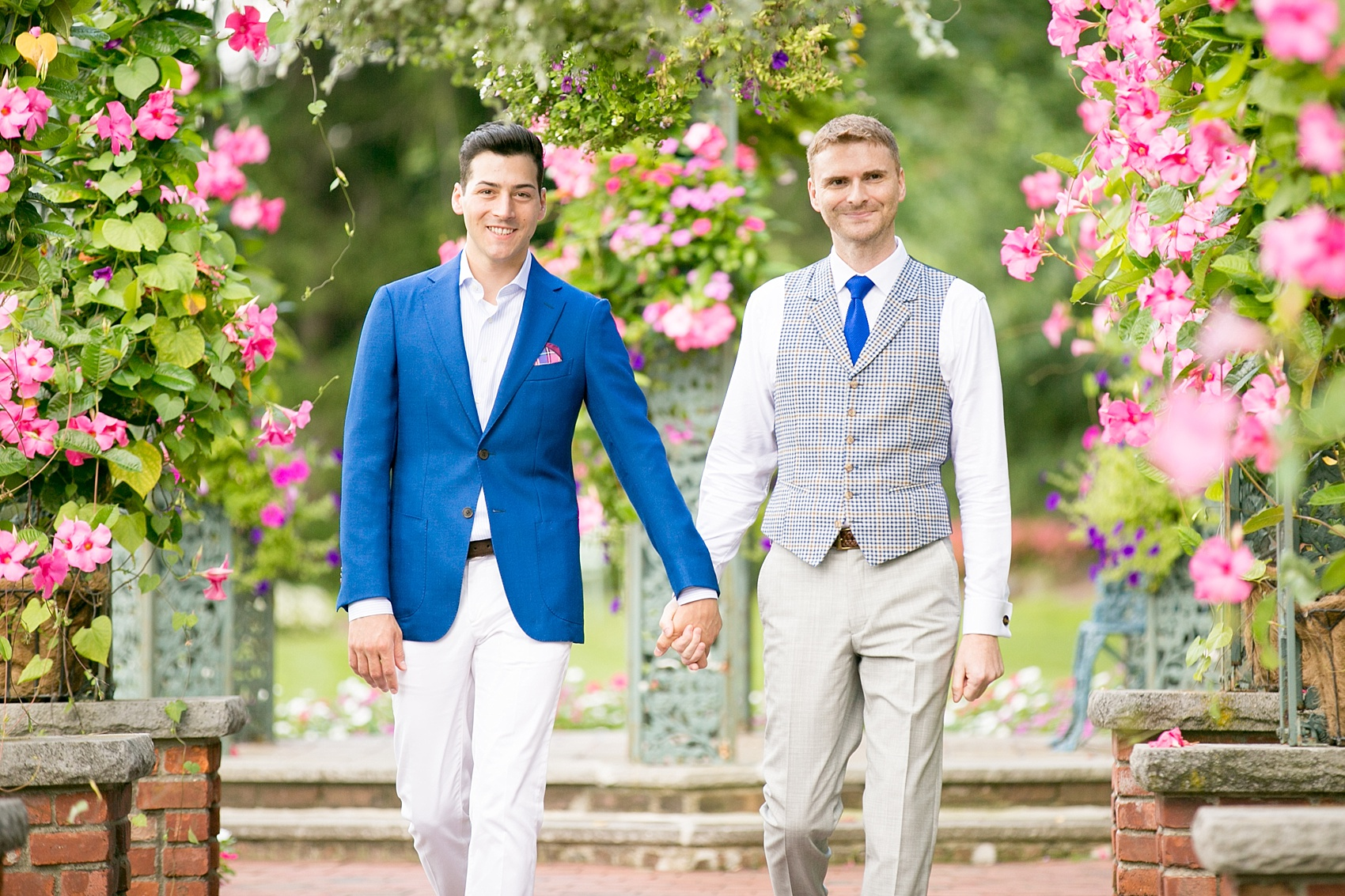 Mikkel Paige Photography photos of a gay wedding at The Manor in West Orange, NJ. The grooms walk to their outdoor summer ceremony on a rose petal carpet under live arches and greenery.