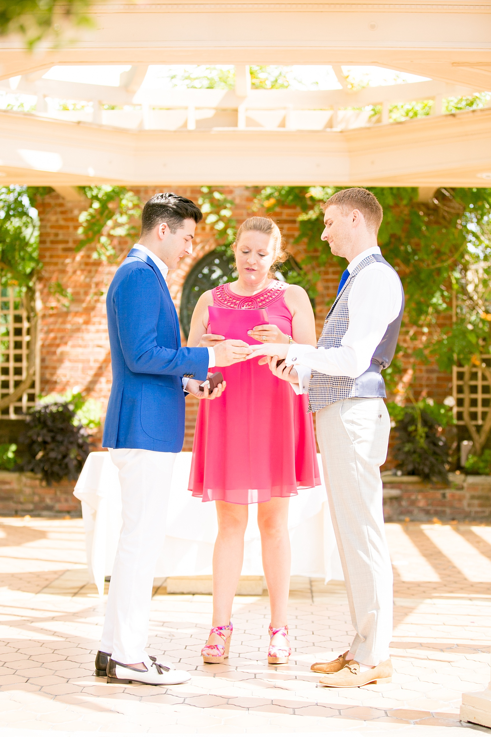 Mikkel Paige Photography photos of a gay wedding at The Manor in West Orange, NJ. Image of grooms exchanging rings during their outdoor ceremony.
