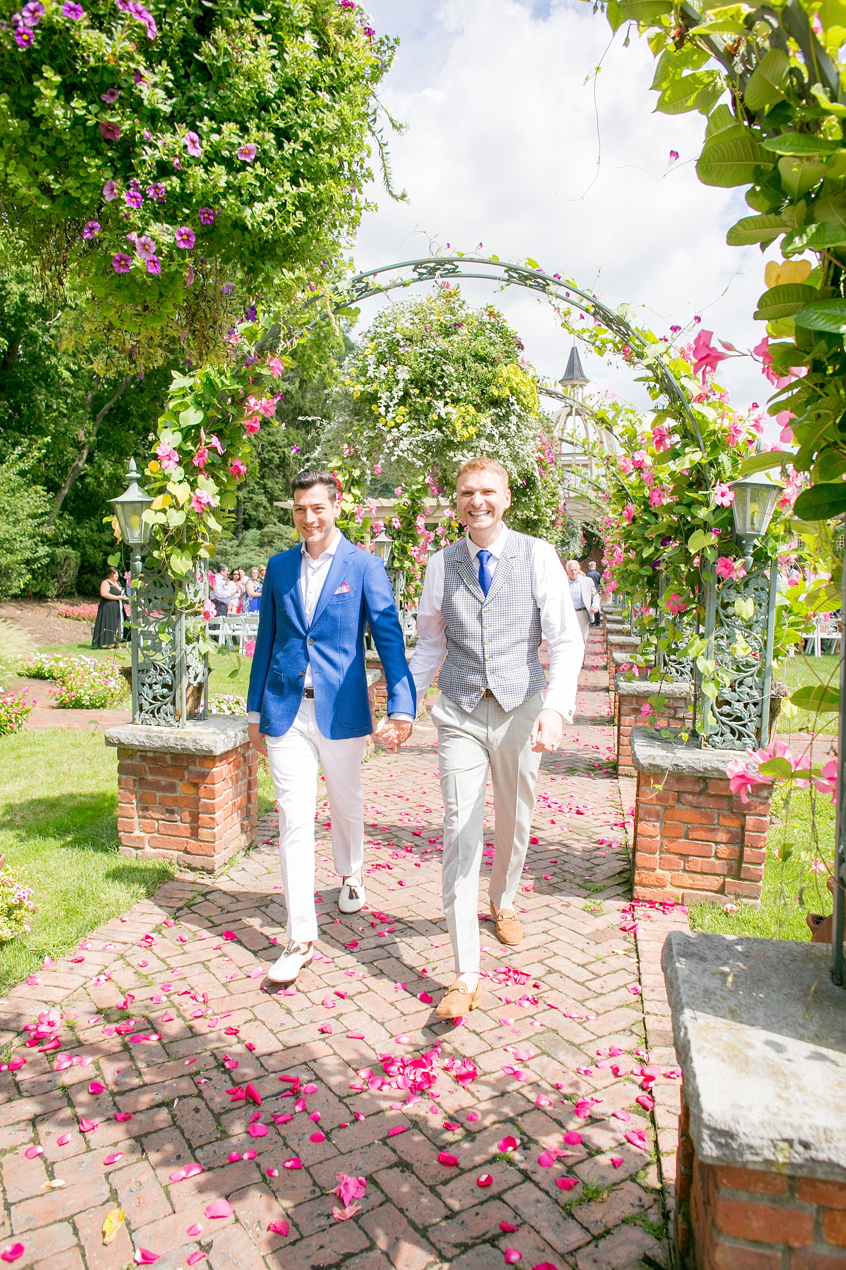 Mikkel Paige Photography photos of a gay wedding at The Manor in West Orange, NJ. The grooms walk from their outdoor summer ceremony on a rose petal carpet under live arches and greenery.