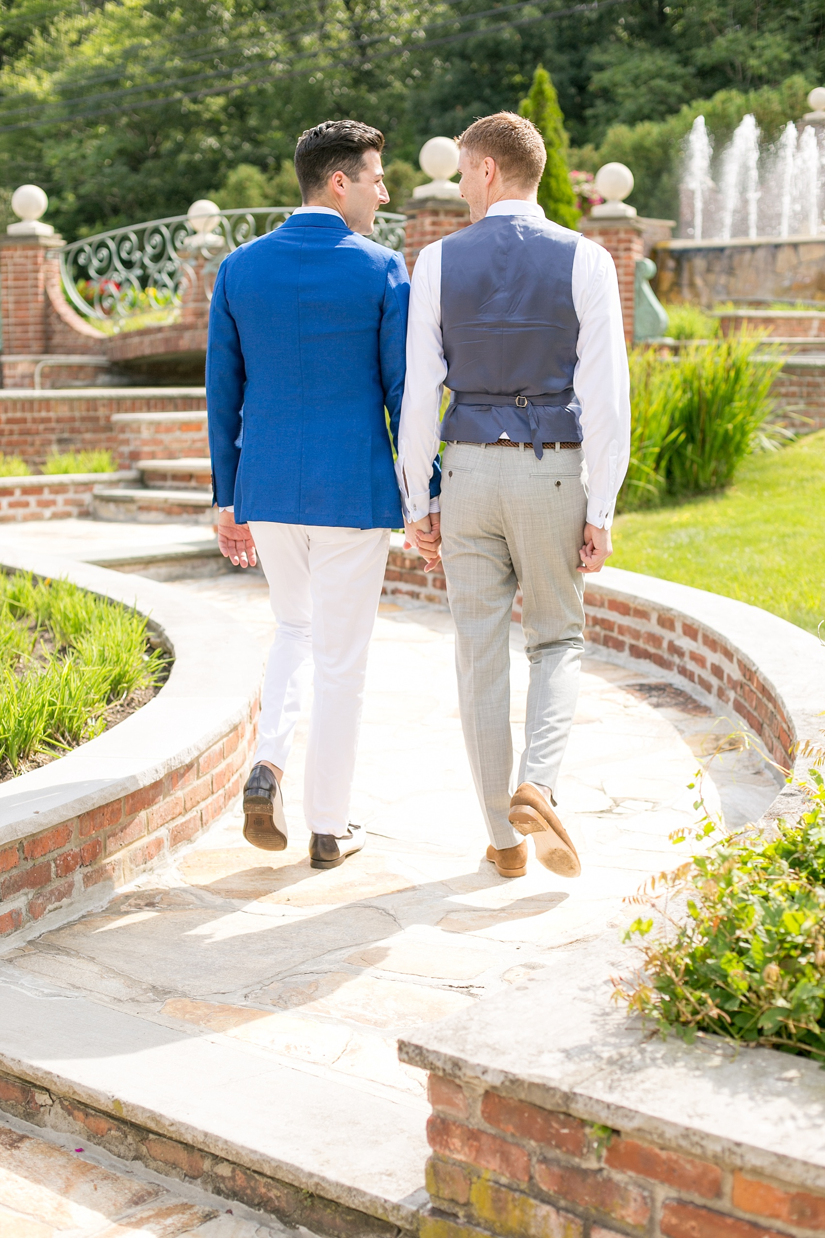 Mikkel Paige Photography photos of a summer, daytime gay wedding. An image of the grooms walking at their venue, The Manor, in West Orange New Jersey.
