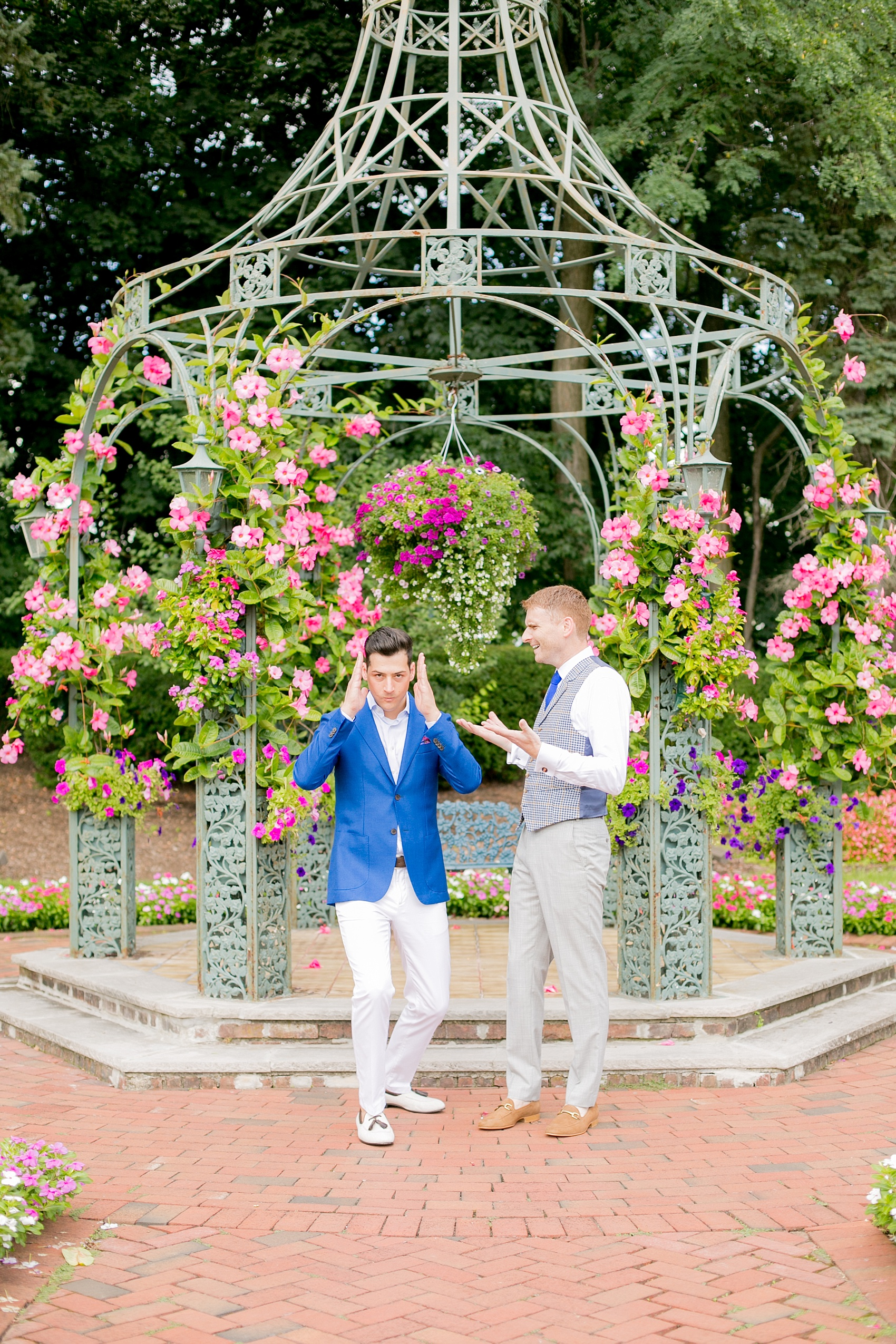 Mikkel Paige Photography photos of a summer, daytime gay wedding. An image of the grooms in a vest and blue suit in front of a trellis dome with pink and green landscaping at The Manor, in West Orange New Jersey.