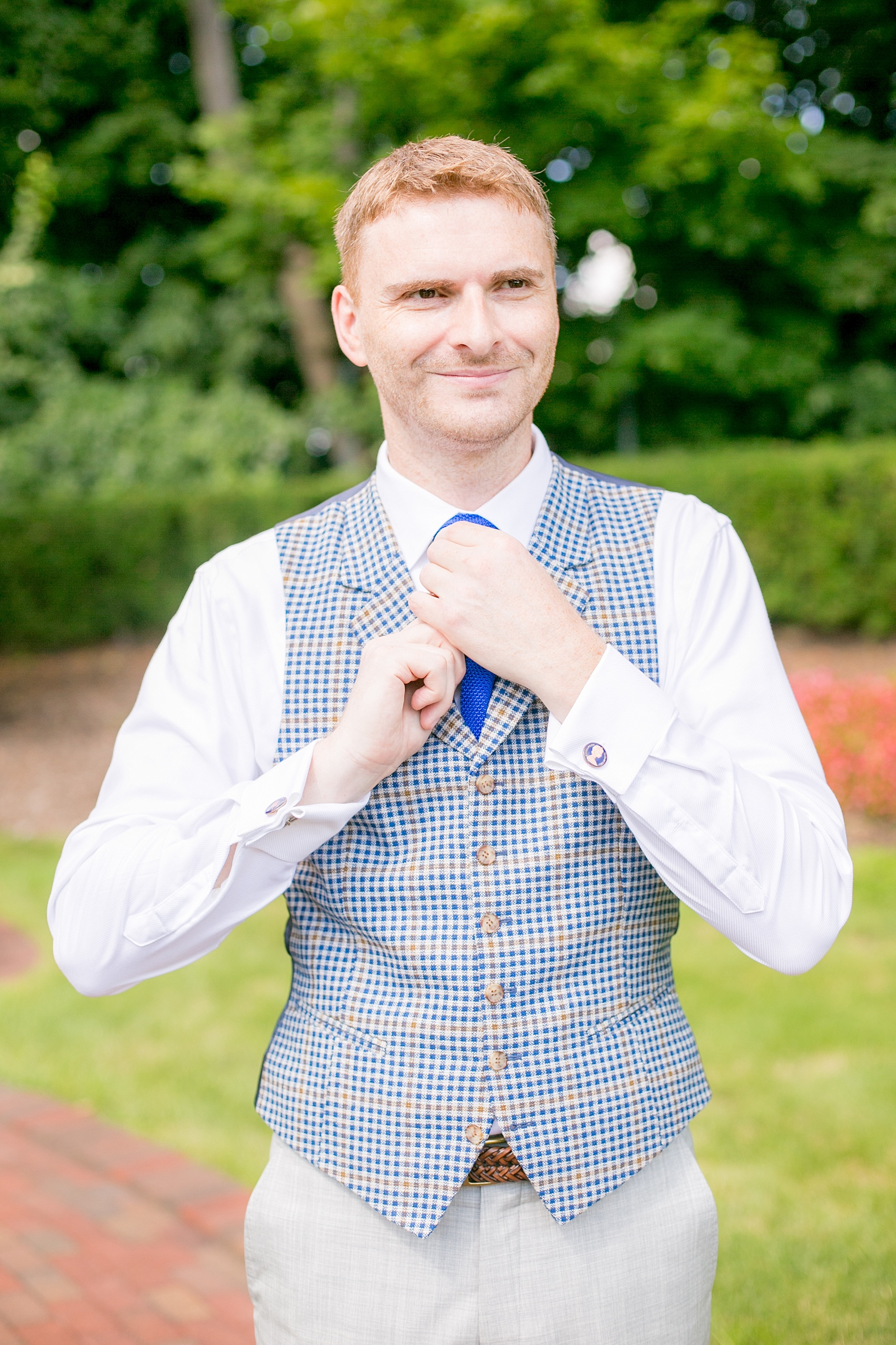 Mikkel Paige Photography photos of a summer, daytime gay wedding. An image of the groom in a blue and white plaid vest at The Manor, in West Orange New Jersey.