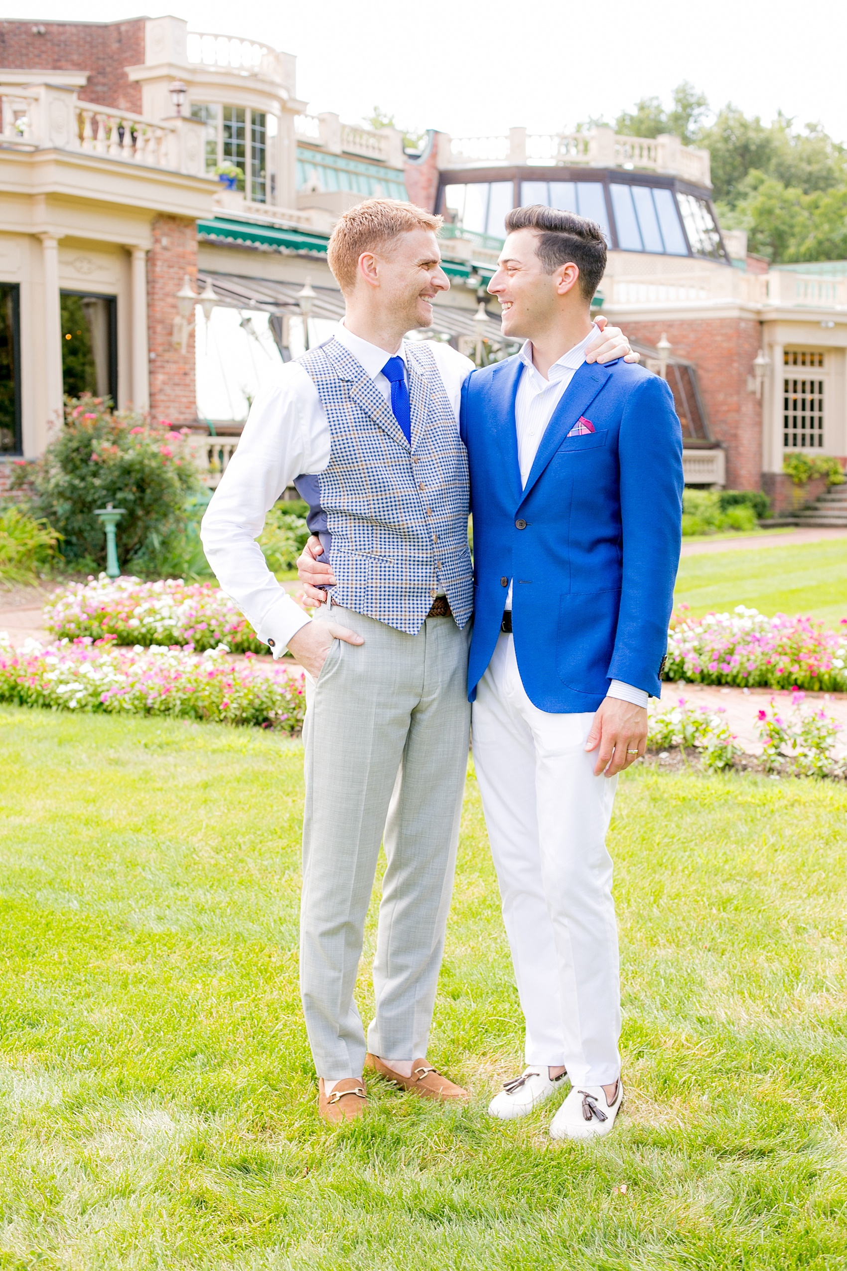 Mikkel Paige Photography photos of a summer, daytime gay wedding. An image of the grooms in a vest and blue suit in front of picturesque landscaping at The Manor, in West Orange New Jersey.