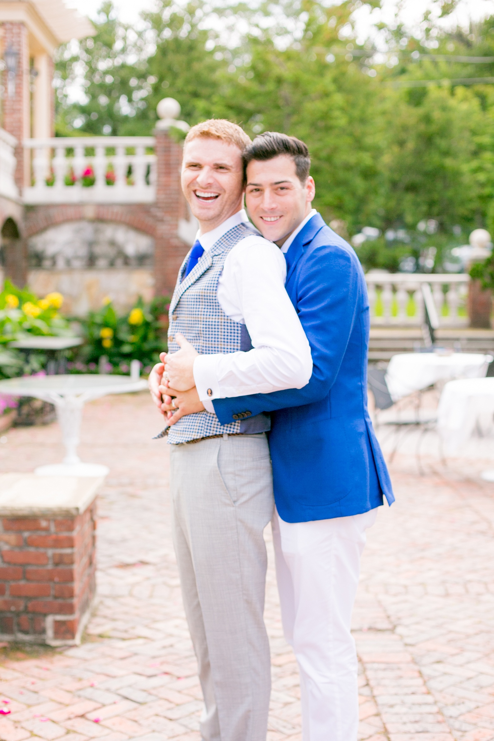 Mikkel Paige Photography photos of a summer, daytime gay wedding. A romantic, playful image of the grooms hugging in a vest and blue suit in front of picturesque landscaping at The Manor, in West Orange New Jersey.
