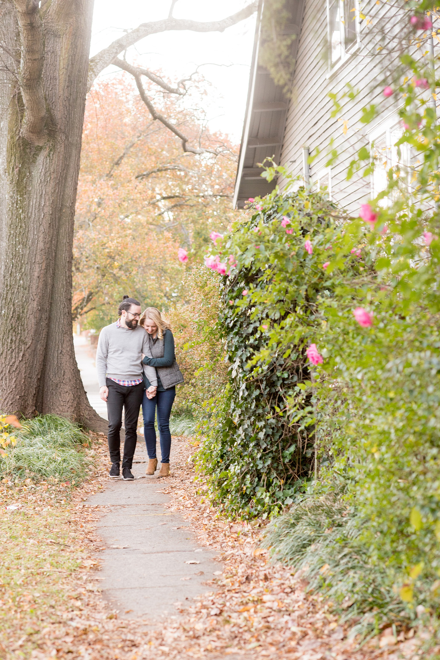 Mikkel Paige Photography photos of a downtown Durham engagement session amidst fall colors and pink rose bushes.