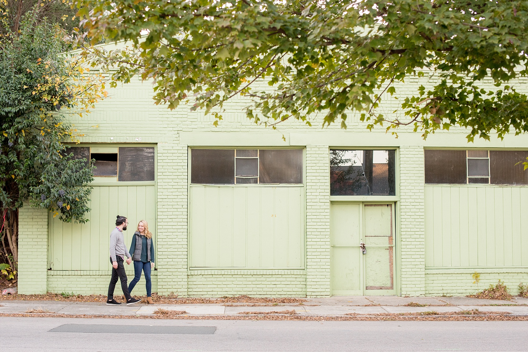 Mikkel Paige Photography photos of a downtown Durham engagement session. A picture of the couple walking in front of a mint green aging building.