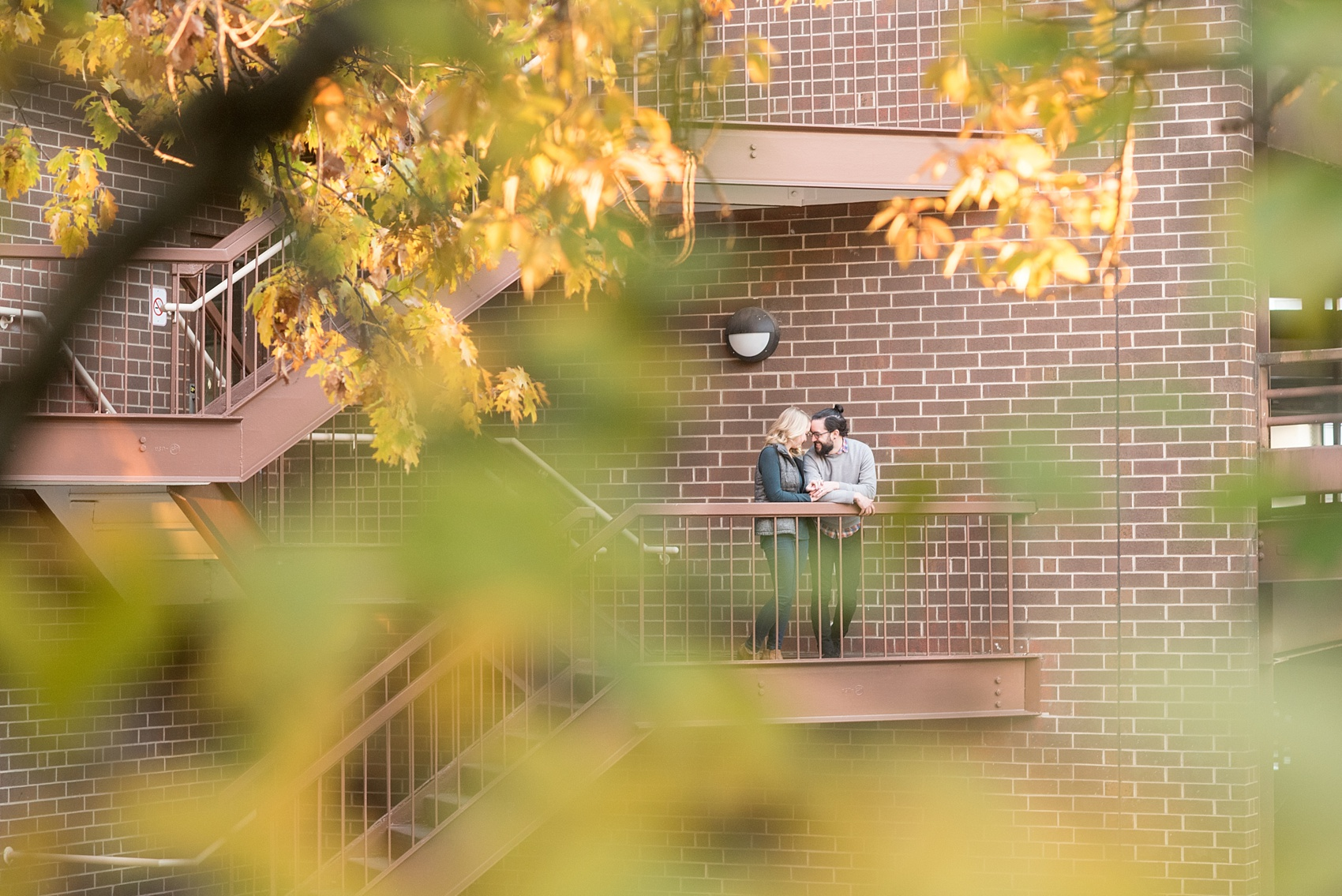 Mikkel Paige Photography photos of a downtown Durham engagement session. A picture of the bride and groom on a balcony peeking through amongst fall leaves.