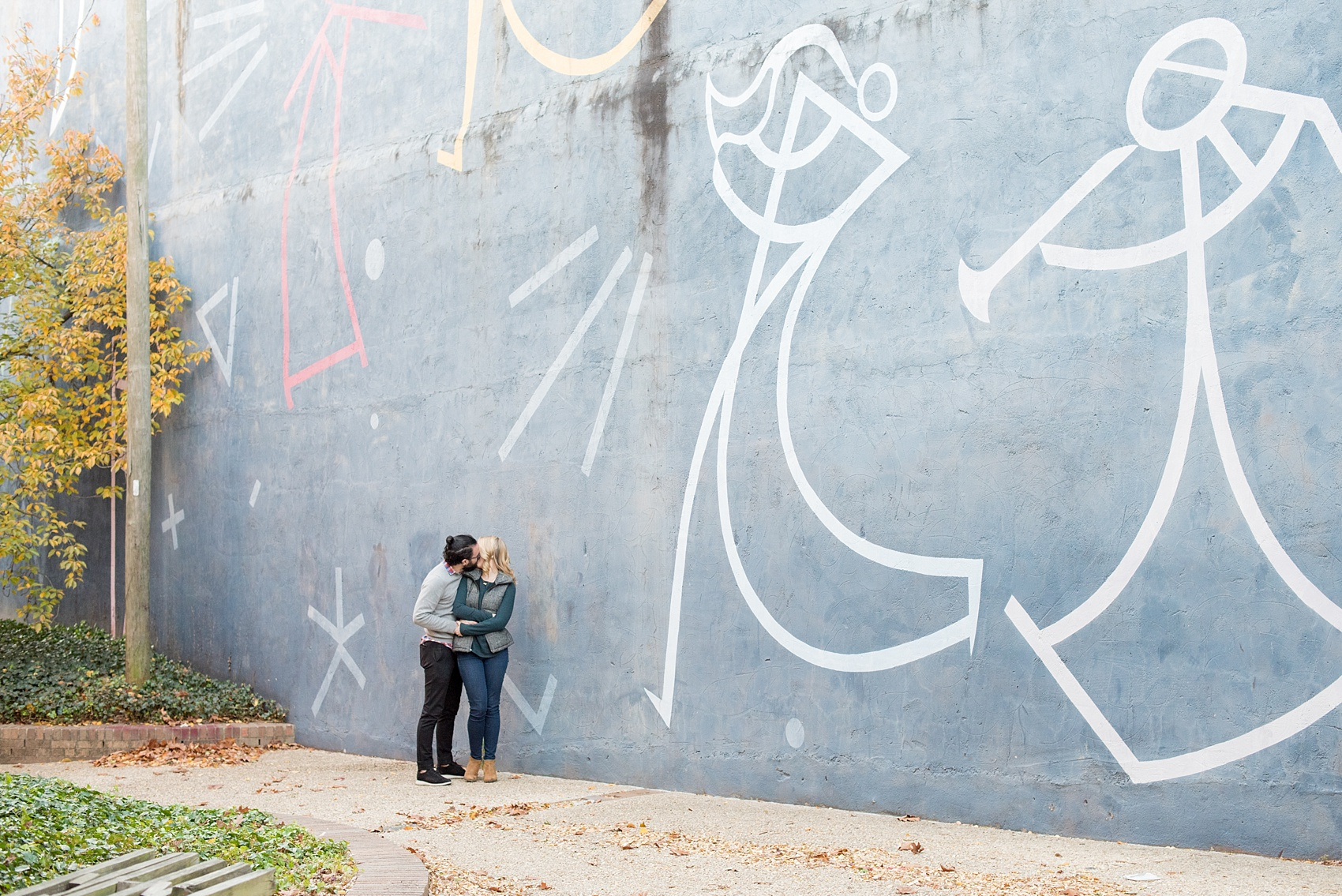 Mikkel Paige Photography photos of a Durham engagement session in downtown Durham against a musical mural.