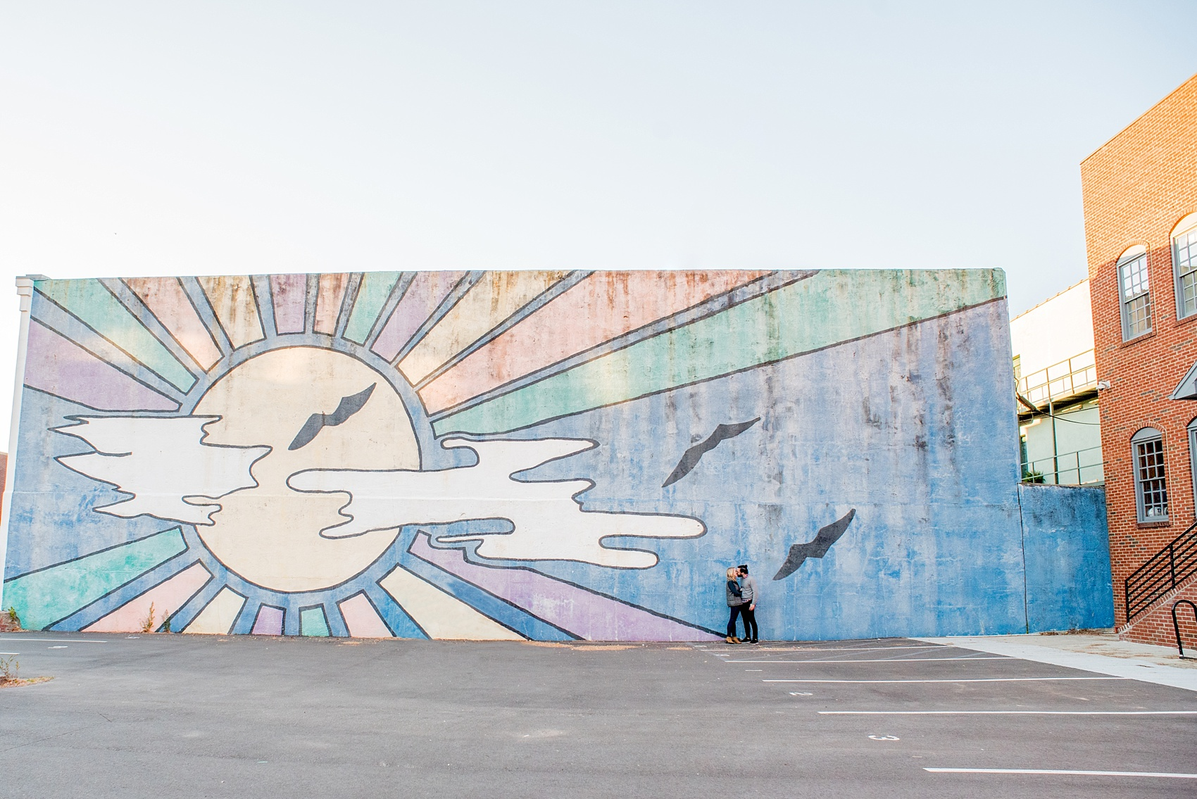 Mikkel Paige Photography photos of a Durham engagement session in downtown Durham against a colorful sun mural.