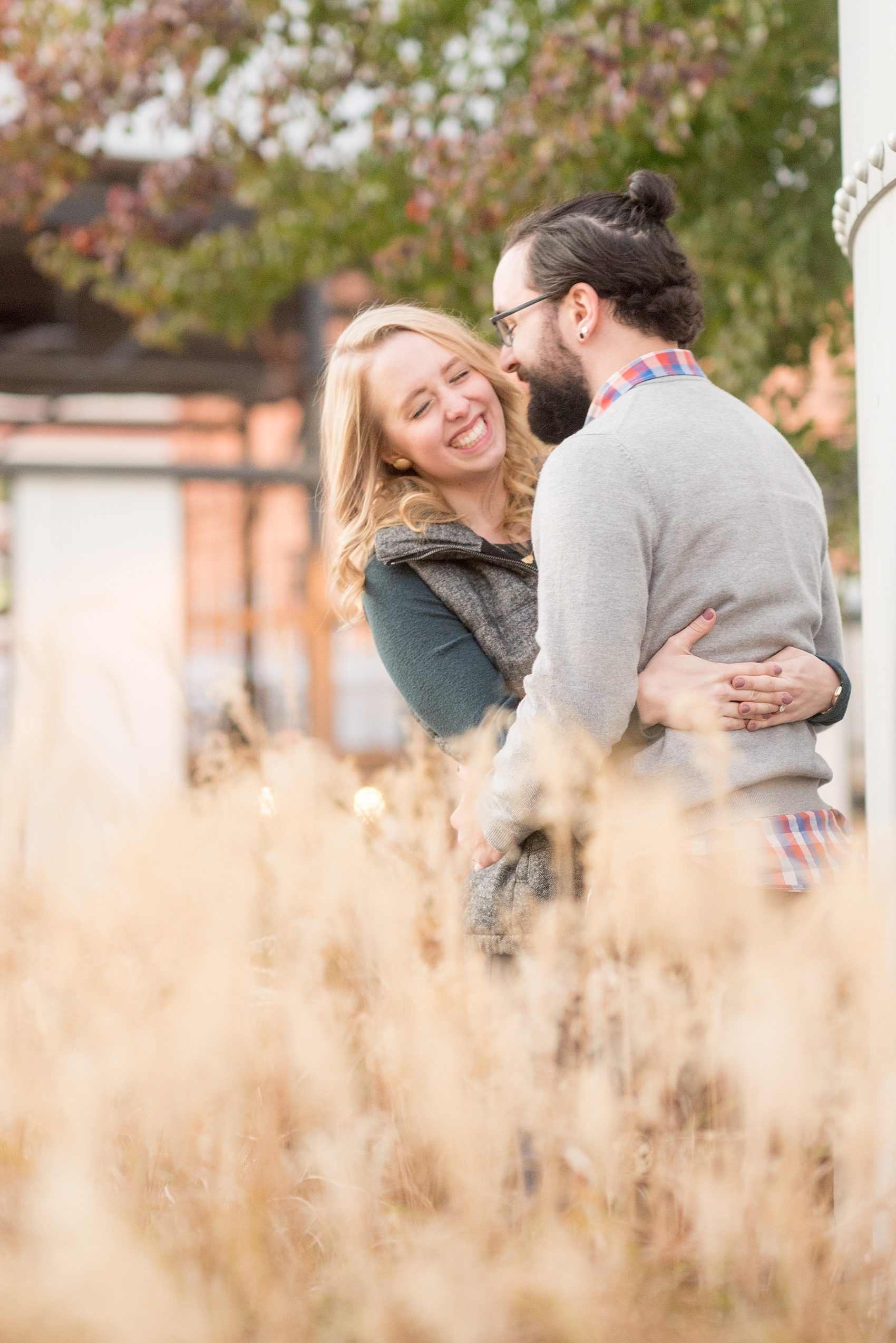Mikkel Paige Photography photos of a Durham engagement session in downtown Durham. The bride and groom got cozy at American Tobacco Campus in this picture amongst the grasses.