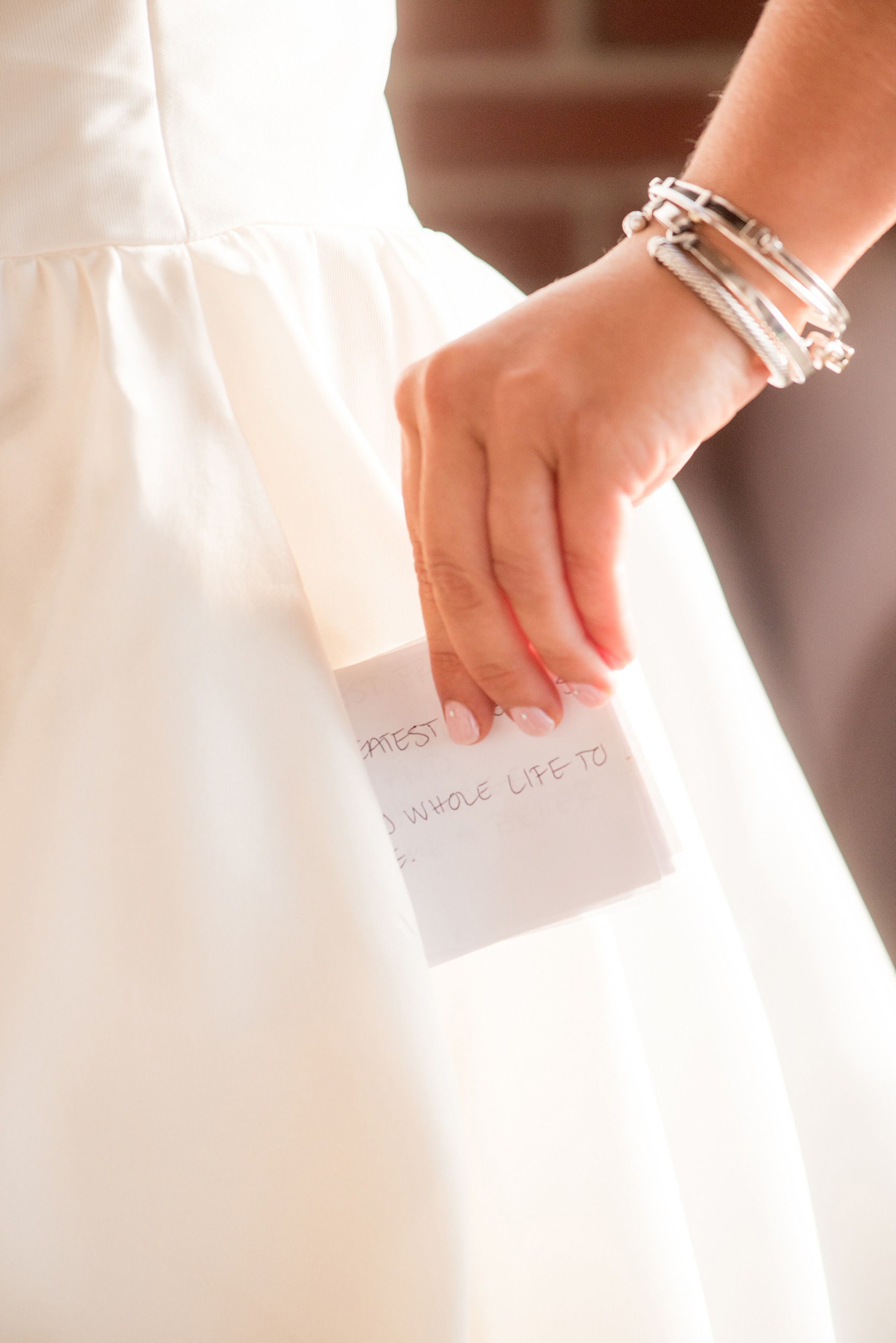 Mikkel Paige Photography photo of a wedding at The Rickhouse, Durham. A picture of the bride's vows being placed in her gown pocket.