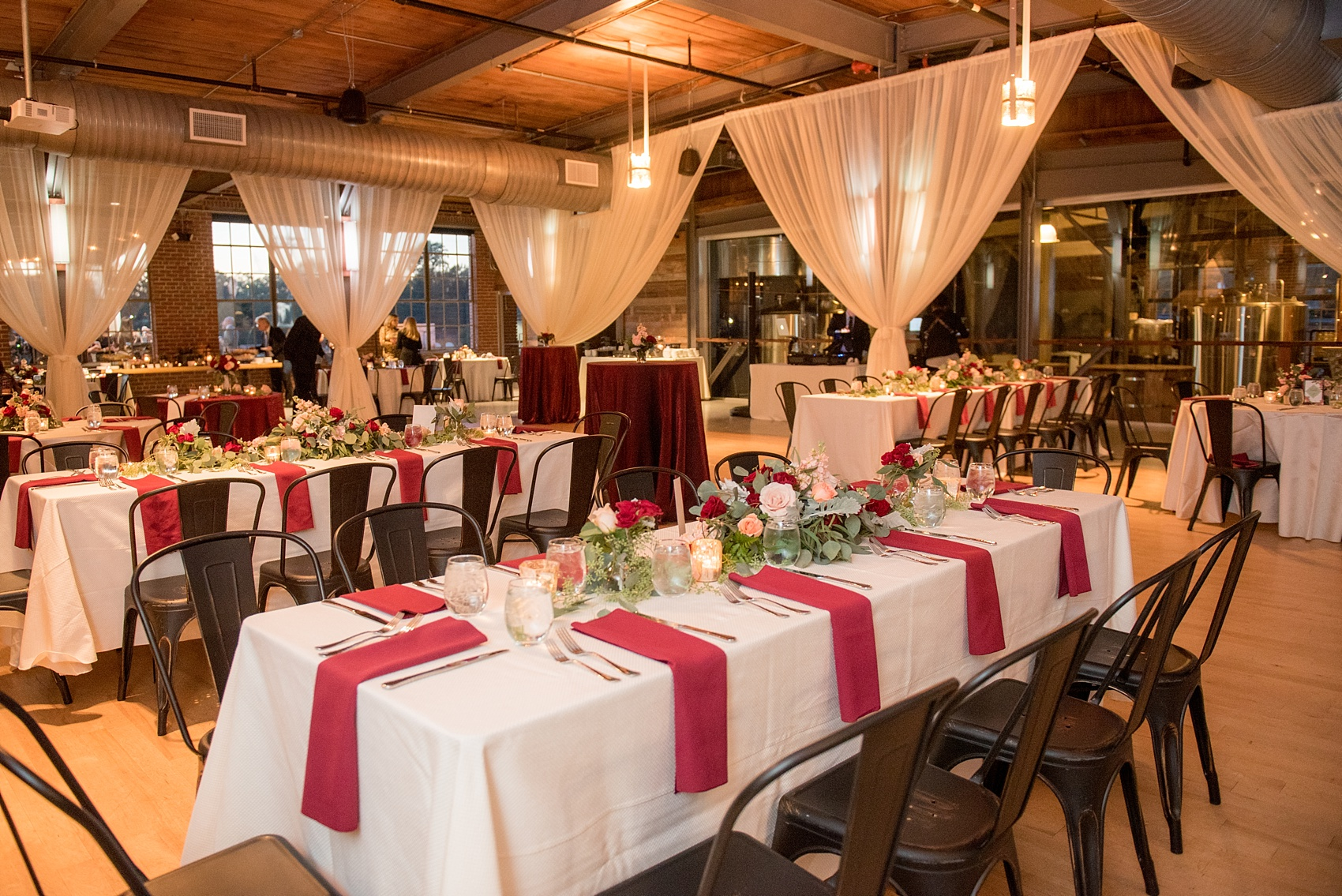 Mikkel Paige Photography photo of a wedding at The Rickhouse, NC. A picture of the rectangular and round mixed tables with burgundy linens and fall flowers and candlelight.