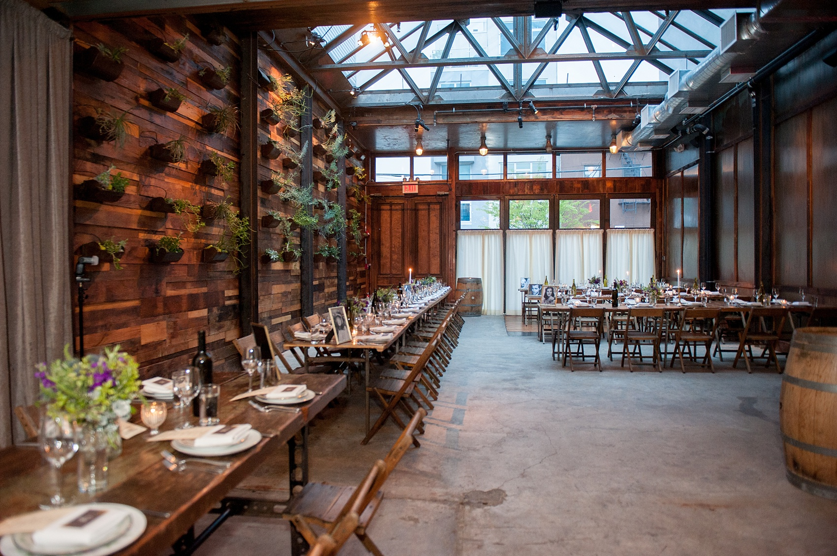 Mikkel Paige Photography Brooklyn Winery wedding photos. Picture of the venue reception area, with farm tables and purple floral centerpieces.