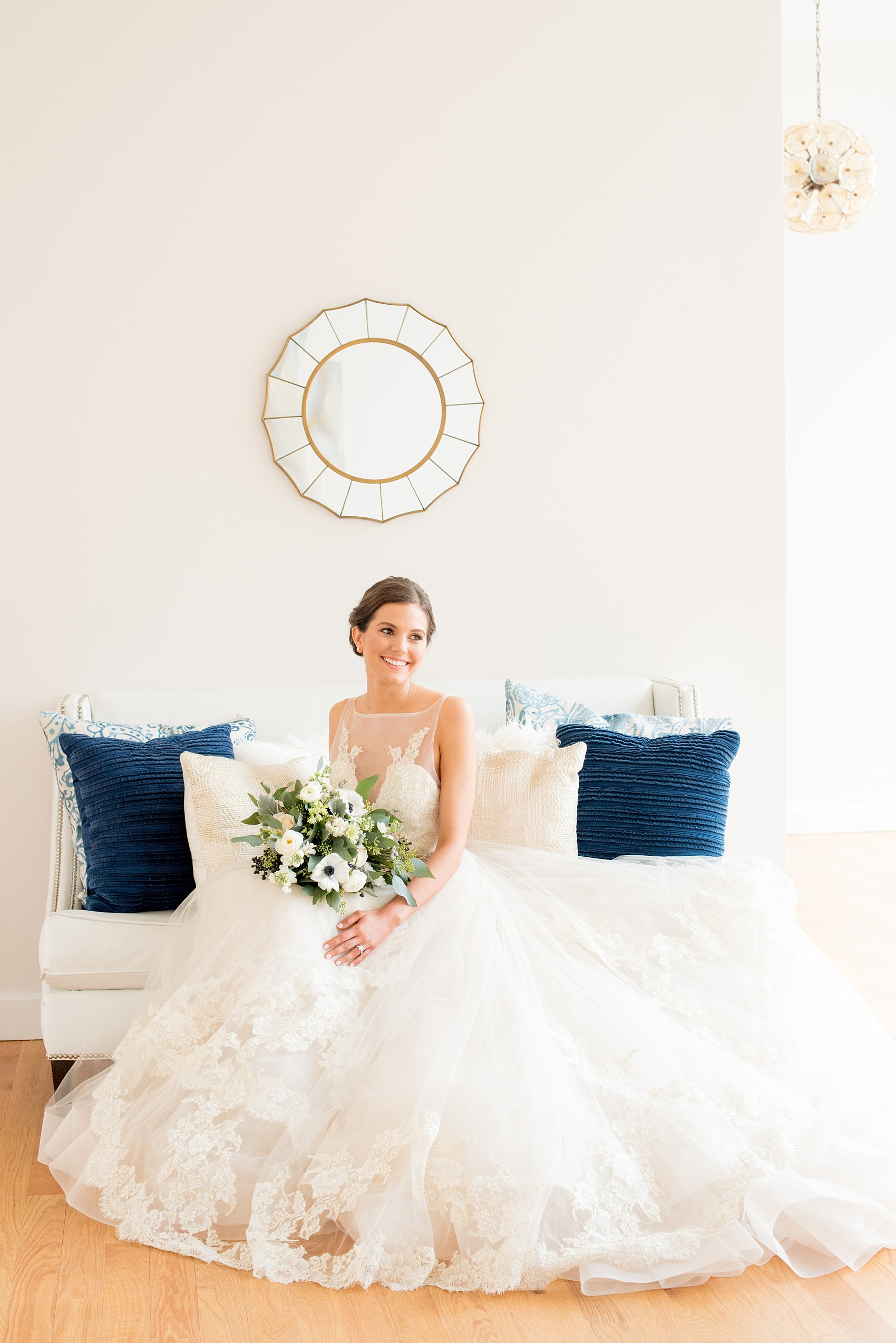 The Glass Box Raleigh wedding photos by Mikkel Paige Photography. Image of a bride in a white gown on a white couch with blue throw pillows.