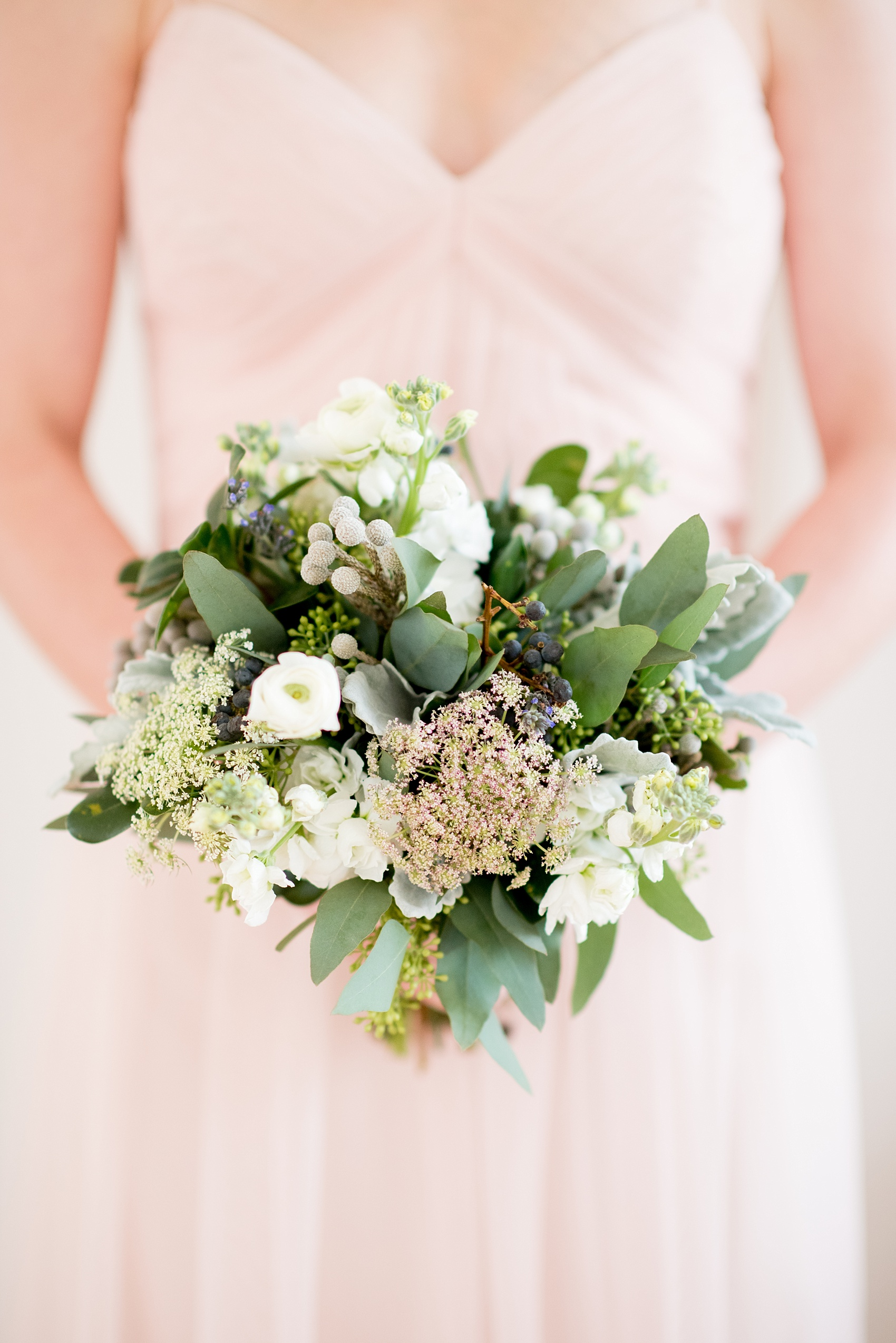 The Glass Box Raleigh wedding photos by Mikkel Paige Photography. Picture of the bridesmaid bouquet of white ranunculus, berries and green eucalyptus.