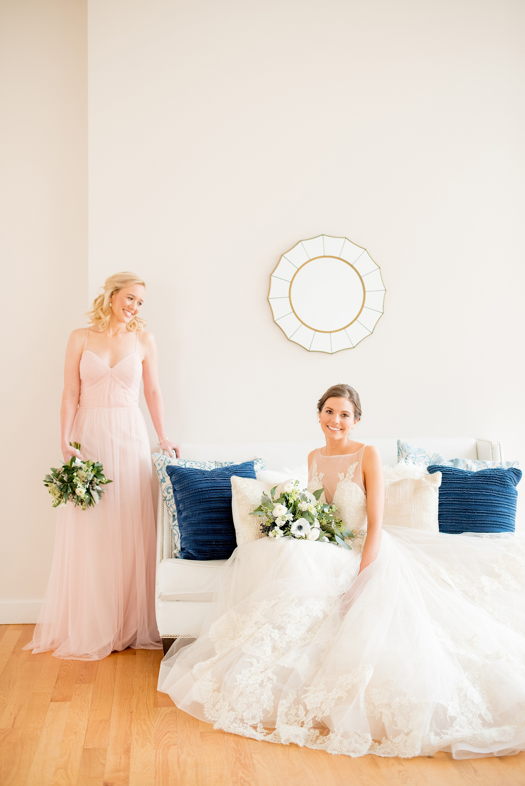 The Glass Box Raleigh wedding photos by Mikkel Paige Photography. Picture of the bride in a Lazaro gown in this modern downtown venue. The bridesmaid wore a pink Hayley Paige occasion gown.