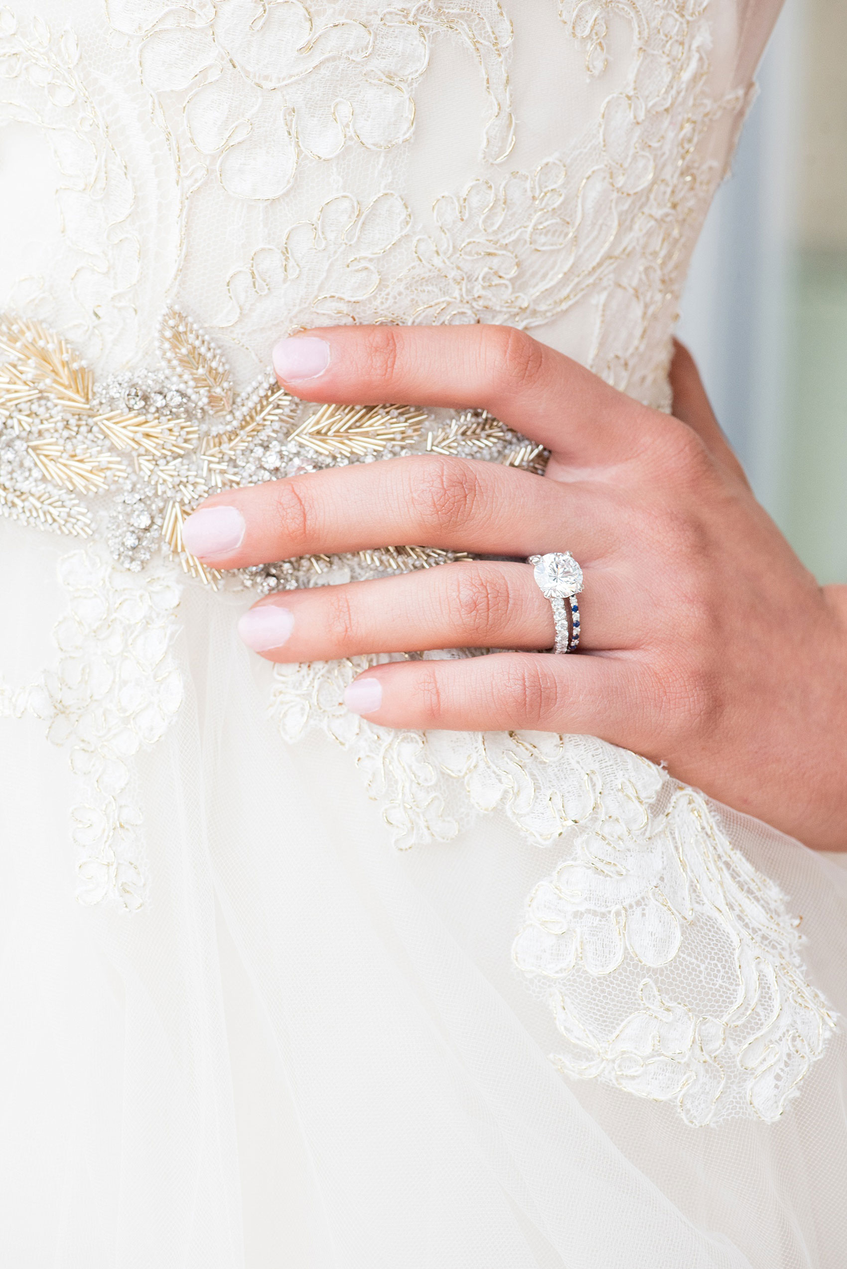 The Glass Box Raleigh wedding photos by Mikkel Paige Photography. Picture of the bride's Lazaro gown beading detail and diamond engagement ring and sapphire band.