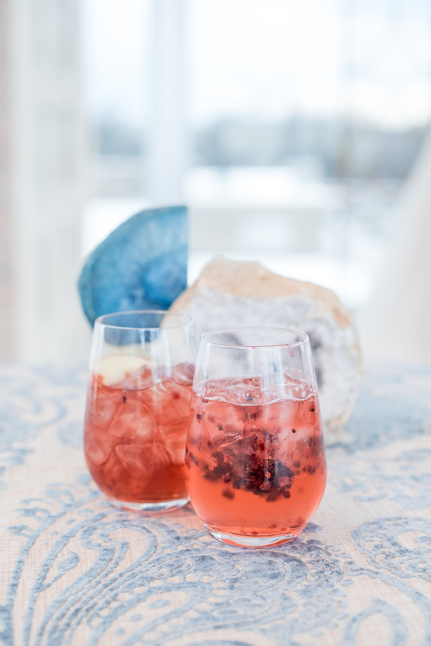 The Glass Box Raleigh wedding photos by Mikkel Paige Photography. Picture of berry cocktails and agate on a blue and white linen. Beverages by On the Rocks bartending in this modern downtown venue in North Carolina.