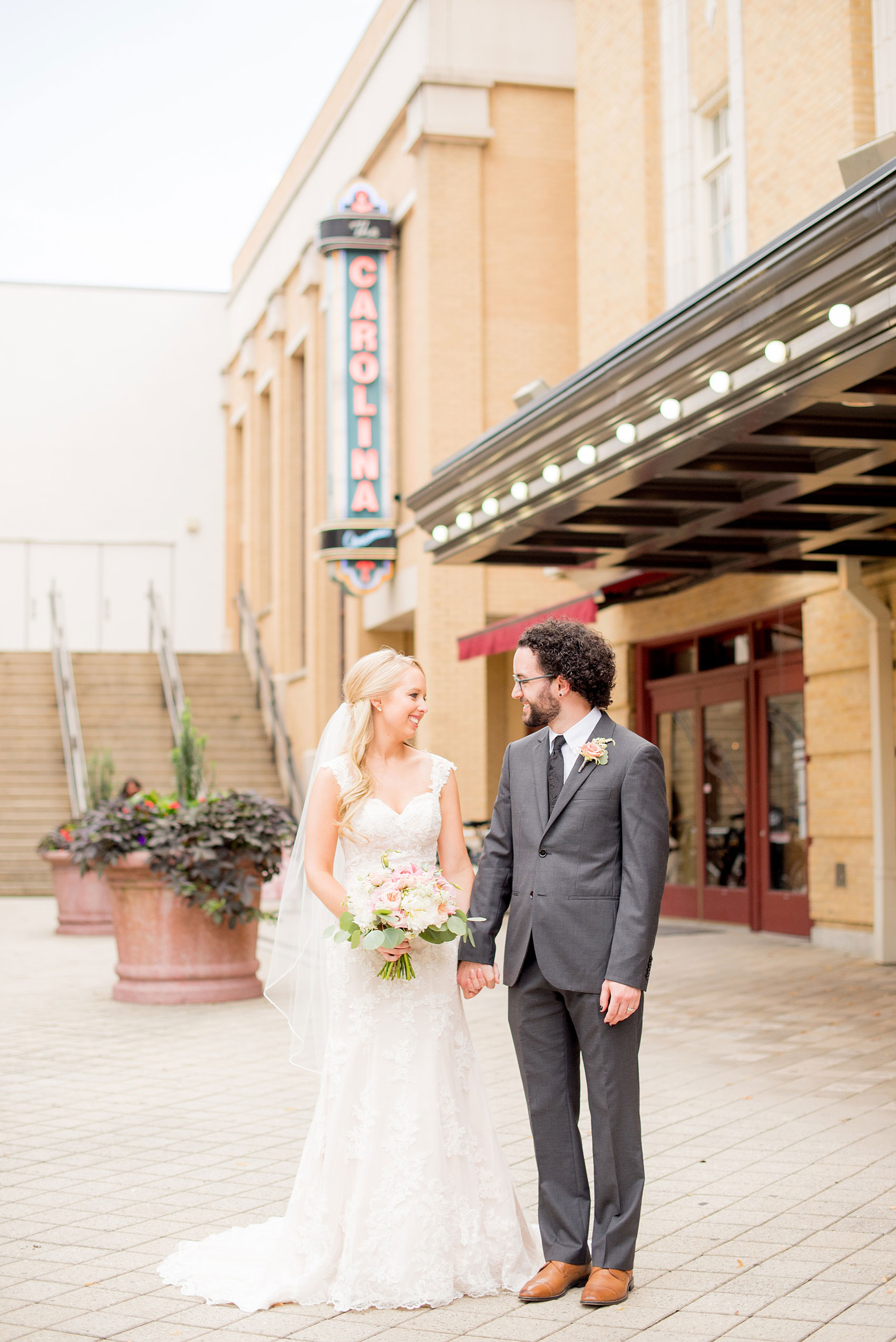 Mikkel Paige Photography photos from a wedding in Durham, North Carolina. Picture of the bride and groom in front of the Carolina sign at a downtown theater.