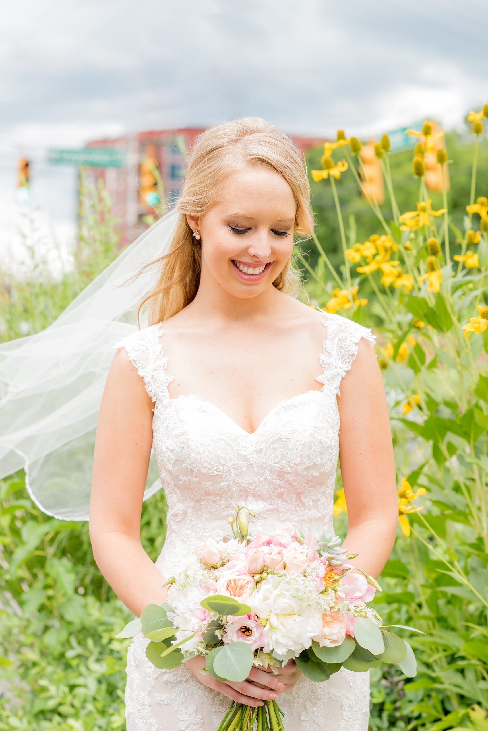 Mikkel Paige Photography photos from a wedding in Durham, North Carolina. Picture of the bride with yellow flowers behind her and veil blowing in the wind. She held a bouquet with peonies, succulents and eucalyptus.
