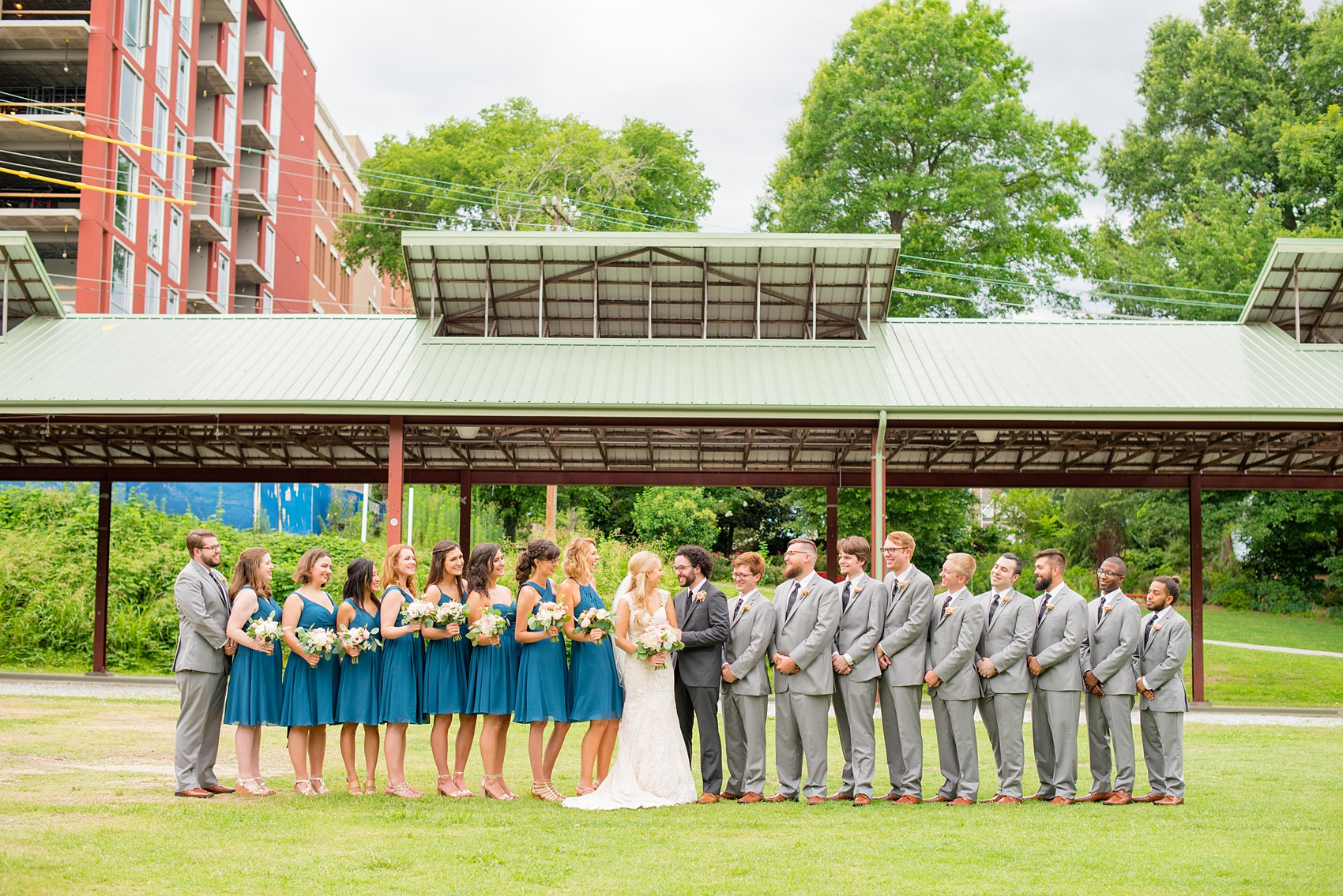 Mikkel Paige Photography photos from a wedding in Durham, North Carolina. Picture of the large wedding party - with the bridesmaids in teal and groomsmen in grey - in a picture in the park.