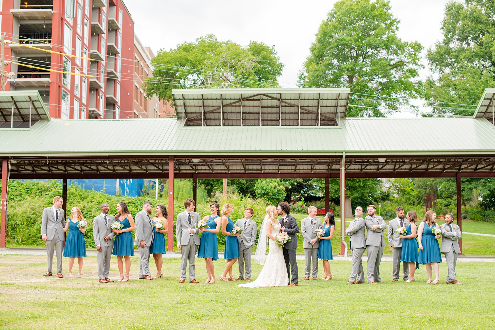 Mikkel Paige Photography photos from a wedding in Durham, North Carolina. Picture of the large wedding party - with the bridesmaids in teal and groomsmen in grey - in a Vogue-like photo in the park.