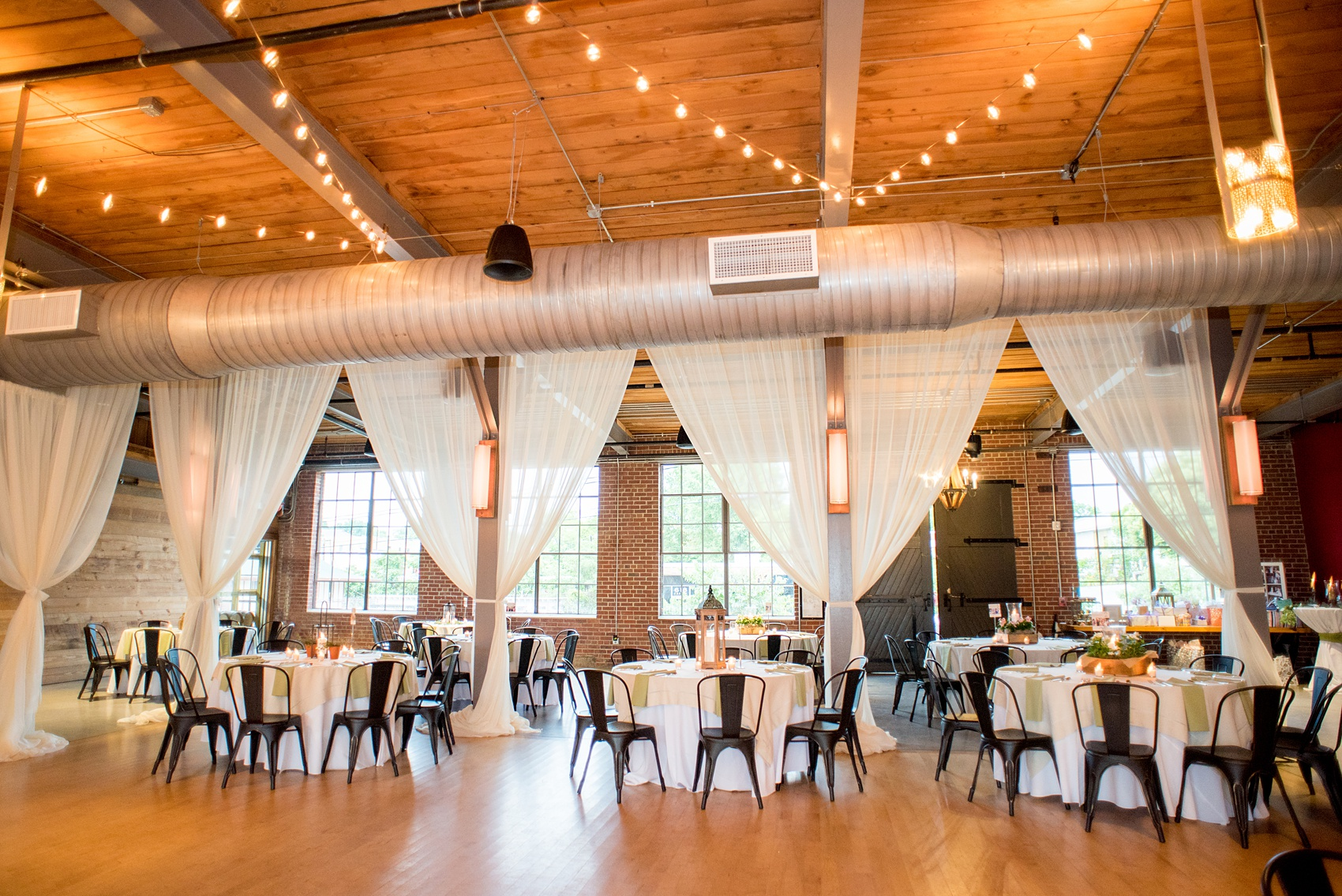 Mikkel Paige Photography photos from a wedding at The Rickhouse in Durham, North Carolina. Picture of the reception setup with metal chairs, draping and rustic lantern centerpieces.