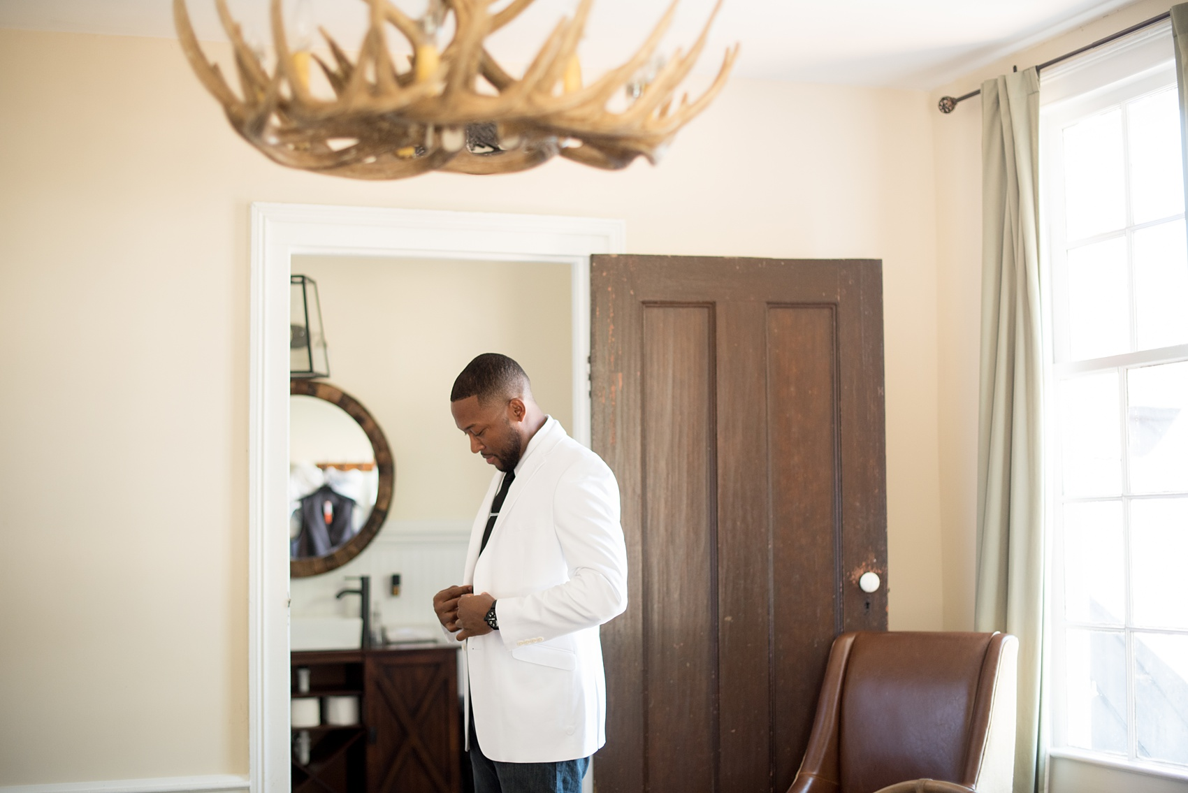 Mikkel Paige Photography pictures of a wedding at Leslie-Alford Mim's House in North Carolina for a Mad Dash Weddings event. Photo of the antler chandelier and getting ready in the groom's suite.