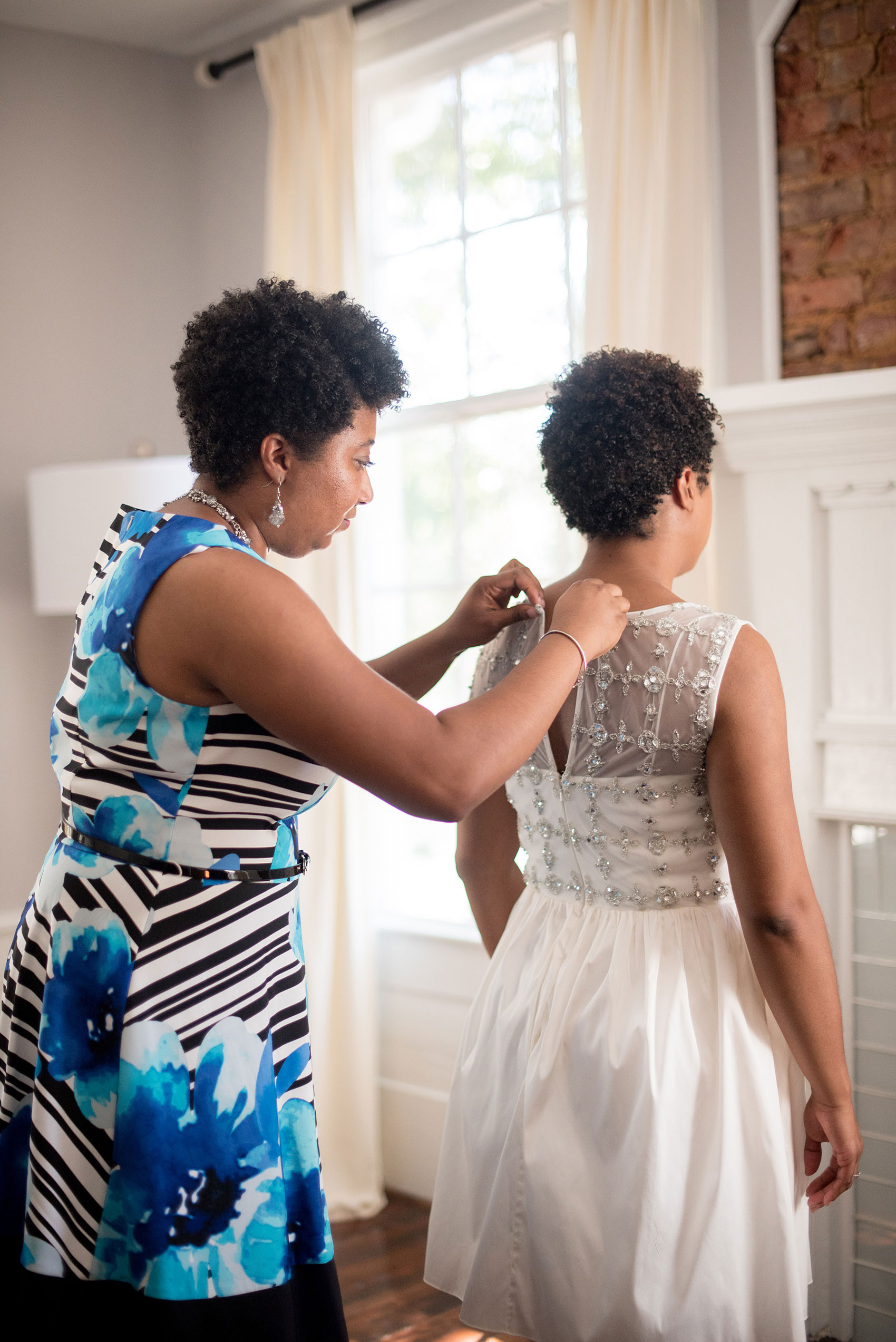 Mikkel Paige Photography pictures of a wedding at Leslie-Alford Mim's House in North Carolina for a Mad Dash Weddings event. Photo of the bride's sister helping her get ready in the bridal suite.