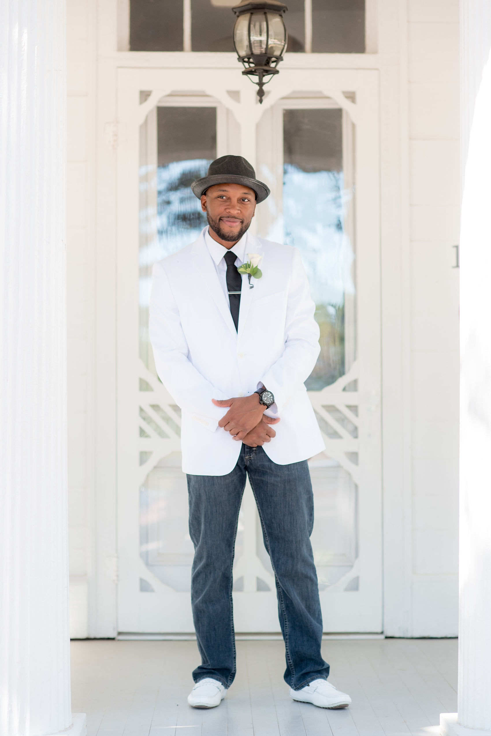Mikkel Paige Photography pictures of a wedding at Leslie-Alford Mim's House in North Carolina for a Mad Dash Weddings event. Photo of the groom in a fedora, white coat and black tie, and casual dark jeans.