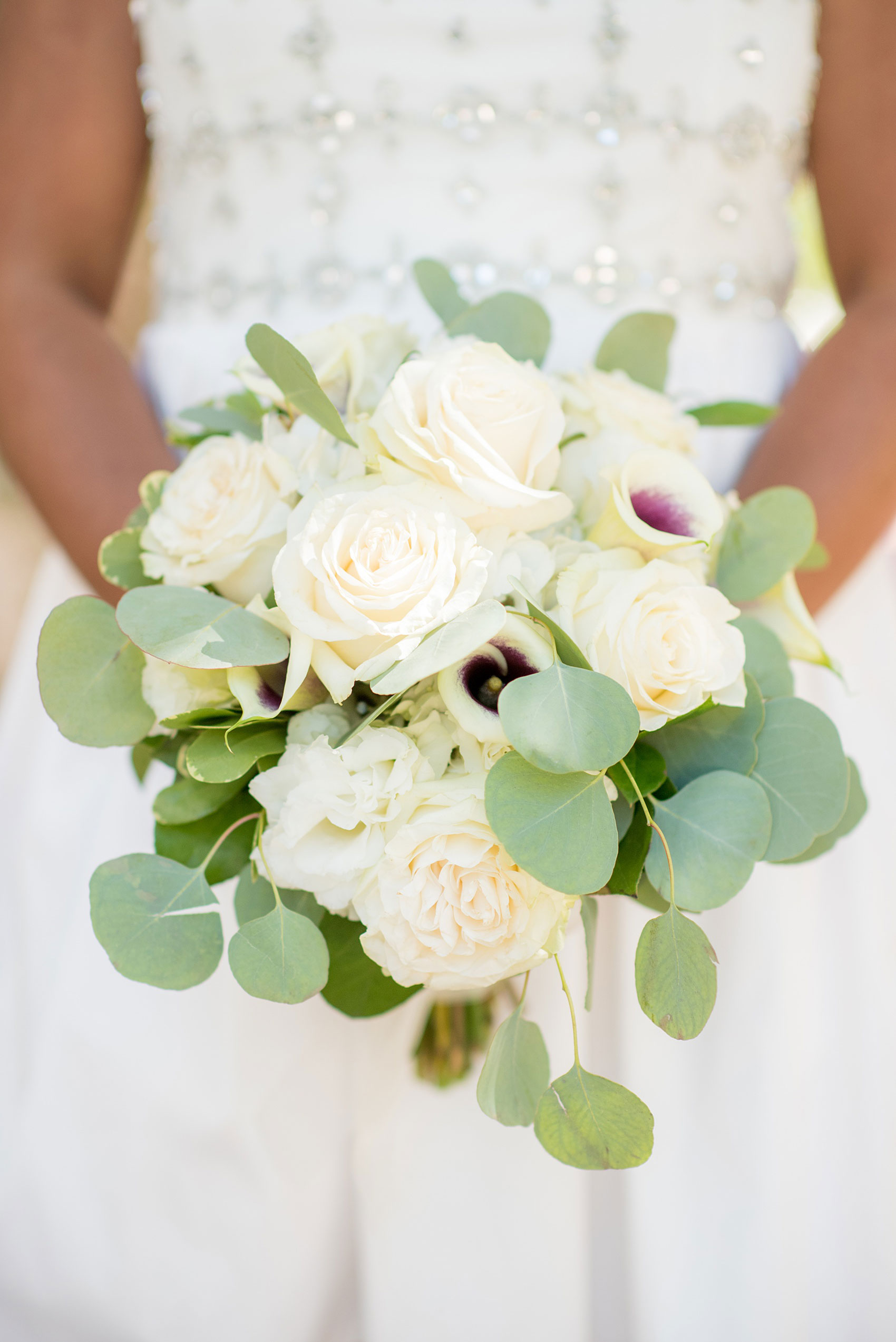 Mikkel Paige Photography pictures of a wedding at Leslie-Alford Mim's House in North Carolina for a Mad Dash Weddings event. Photo of the bride's white rose, Picasso Calla Lily and silver dollar eucalyptus greenery.