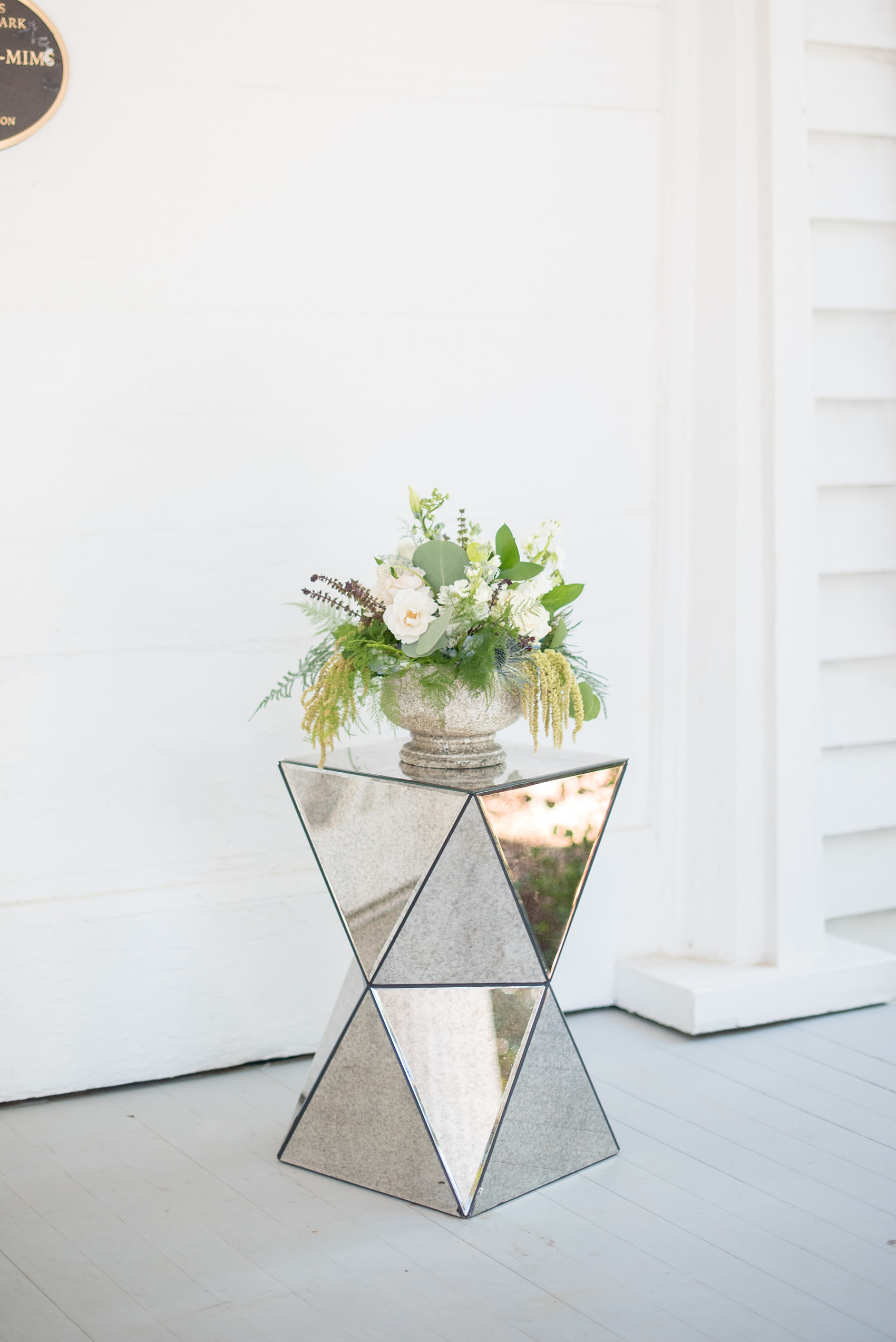 Mikkel Paige Photography pictures of a wedding at Leslie-Alford Mim's House in North Carolina for a Mad Dash Weddings event. Photo of a trendy, angled mirror side table and floral centerpiece.