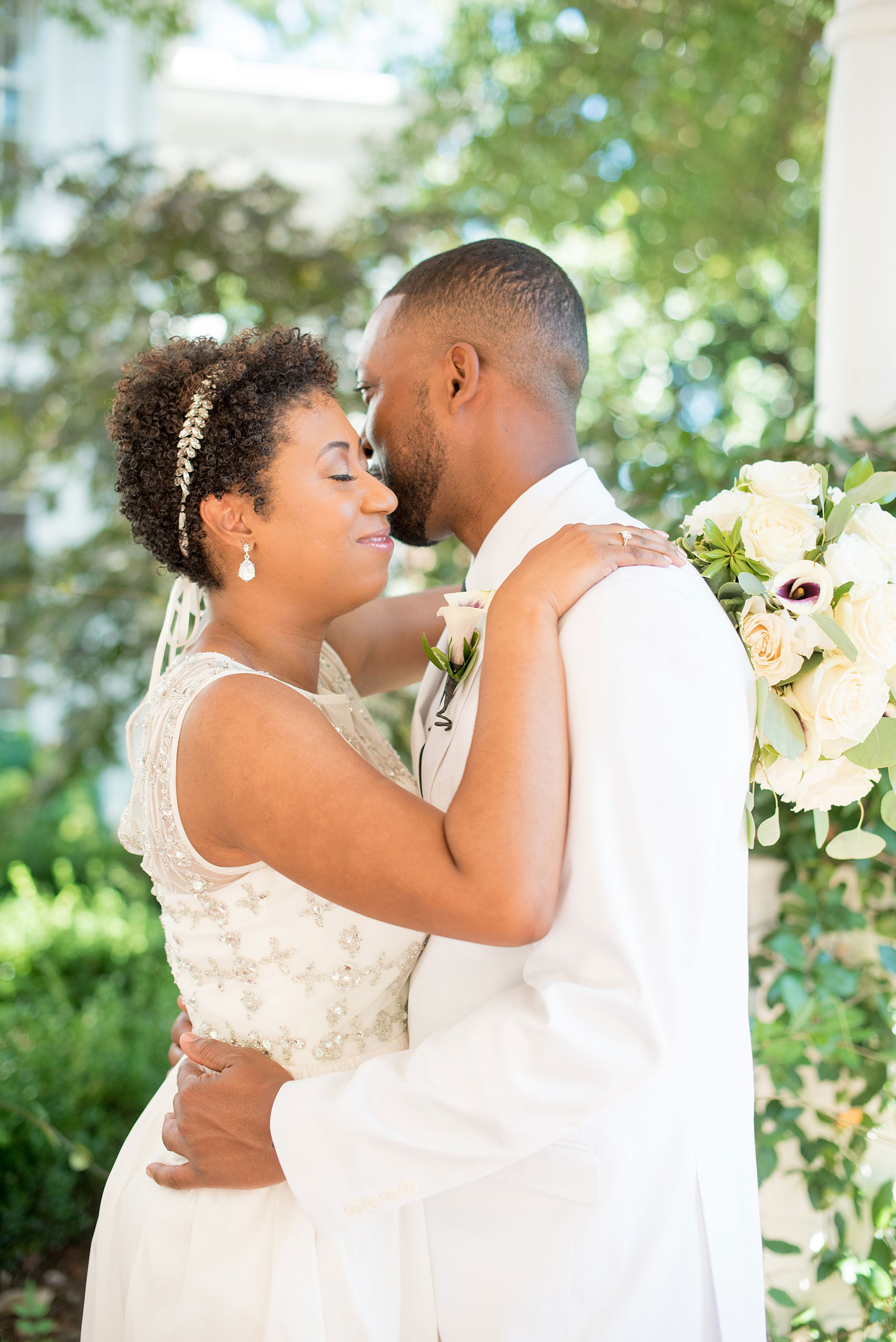 Mikkel Paige Photography pictures of a wedding at Leslie-Alford Mim's House in North Carolina for a Mad Dash Weddings event. Photo of the bride and groom embracing in the garden.