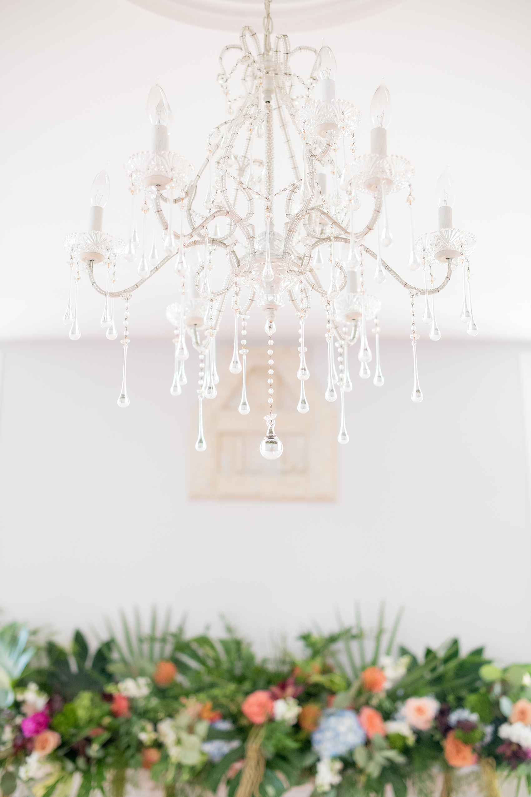 Mikkel Paige Photography pictures of a wedding at Leslie-Alford Mim's House in North Carolina for a Mad Dash Weddings event. Photo of the glass chandelier hanging in the ceremony space.