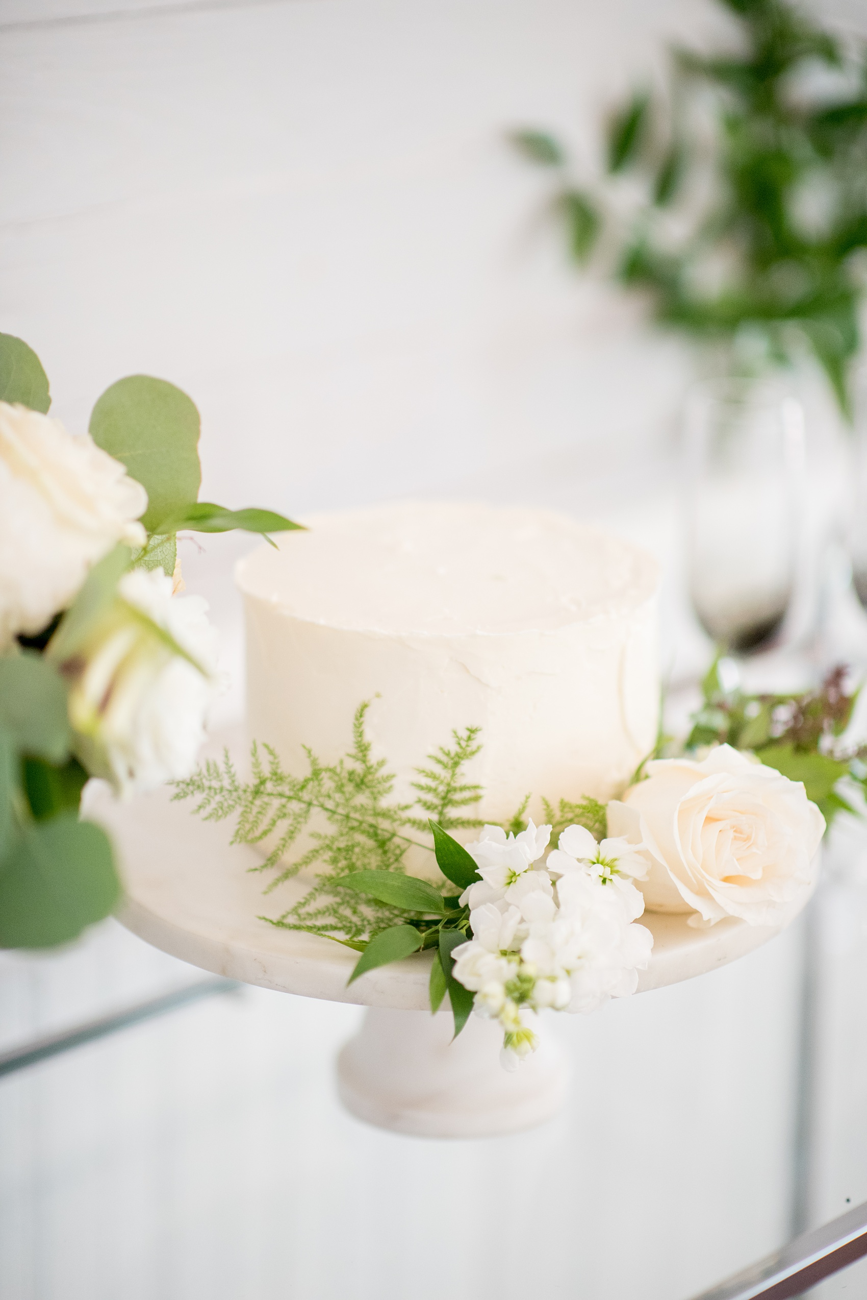 Mikkel Paige Photography pictures of a wedding at Leslie-Alford Mim's House in North Carolina for a Mad Dash Weddings event. Photo of the petite red-velvet, white frosted wedding cake adorned with flowers.